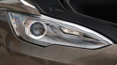 This Tuesday, April 7, 2015 photo shows the front head lamp assembly of a Tesla Model S 70-D electric car, in Detroit. Tesla is going after mainstream luxury car buyers by boosting the range, power and price of its low-end Model S. The $75,000 all-wheel-drive 70-D can go a government-certified 240 miles per charge, has 514 horsepower and can go from zero to 60 in 5.2 seconds. (AP Photo/Carlos Osorio)