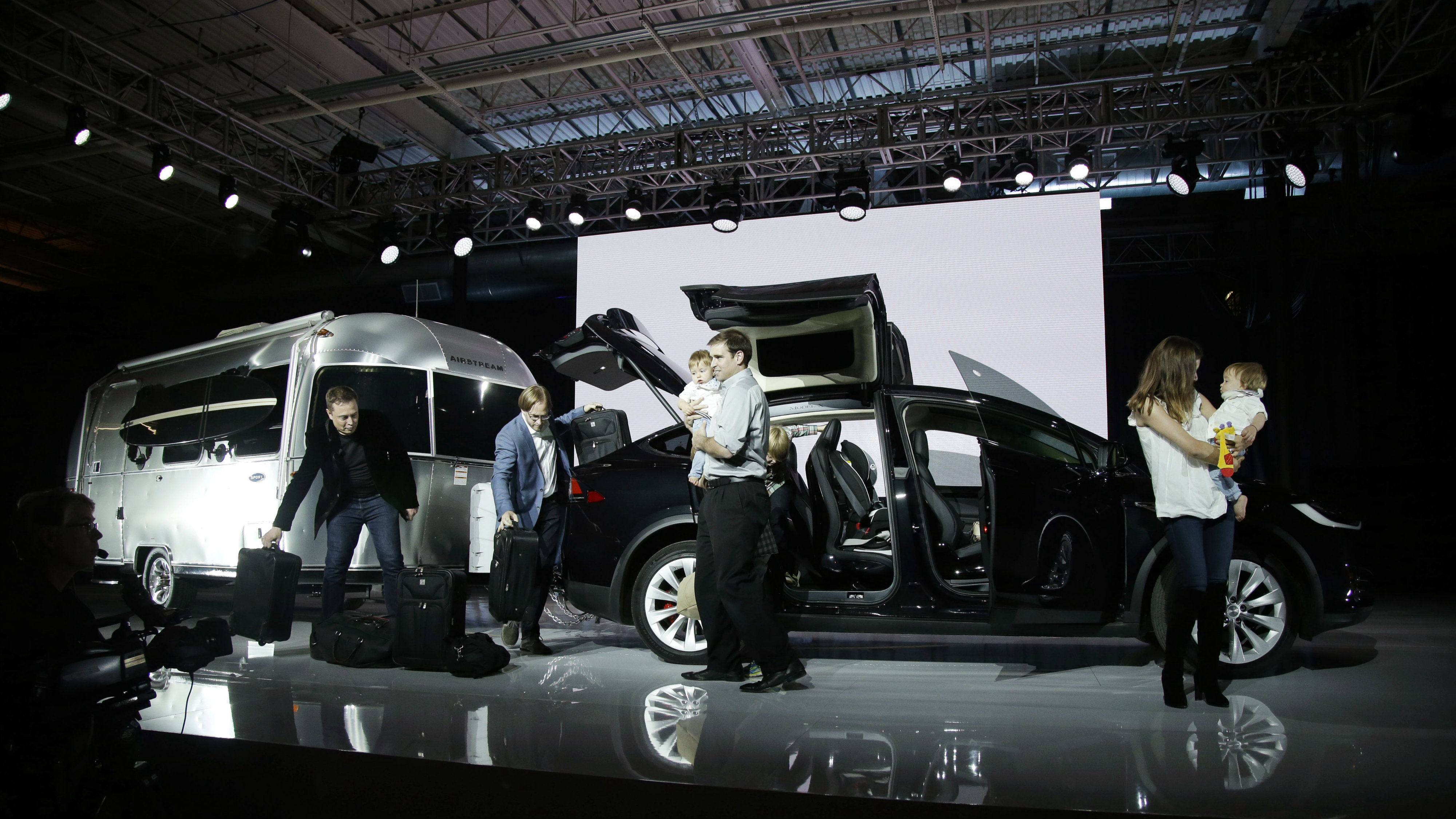 Elon Musk, CEO of Tesla Motors Inc., at left, shows the amount of cargo space on the new Model X car at the company's headquarters Tuesday, Sept. 29, 2015, in Fremont, Calif.