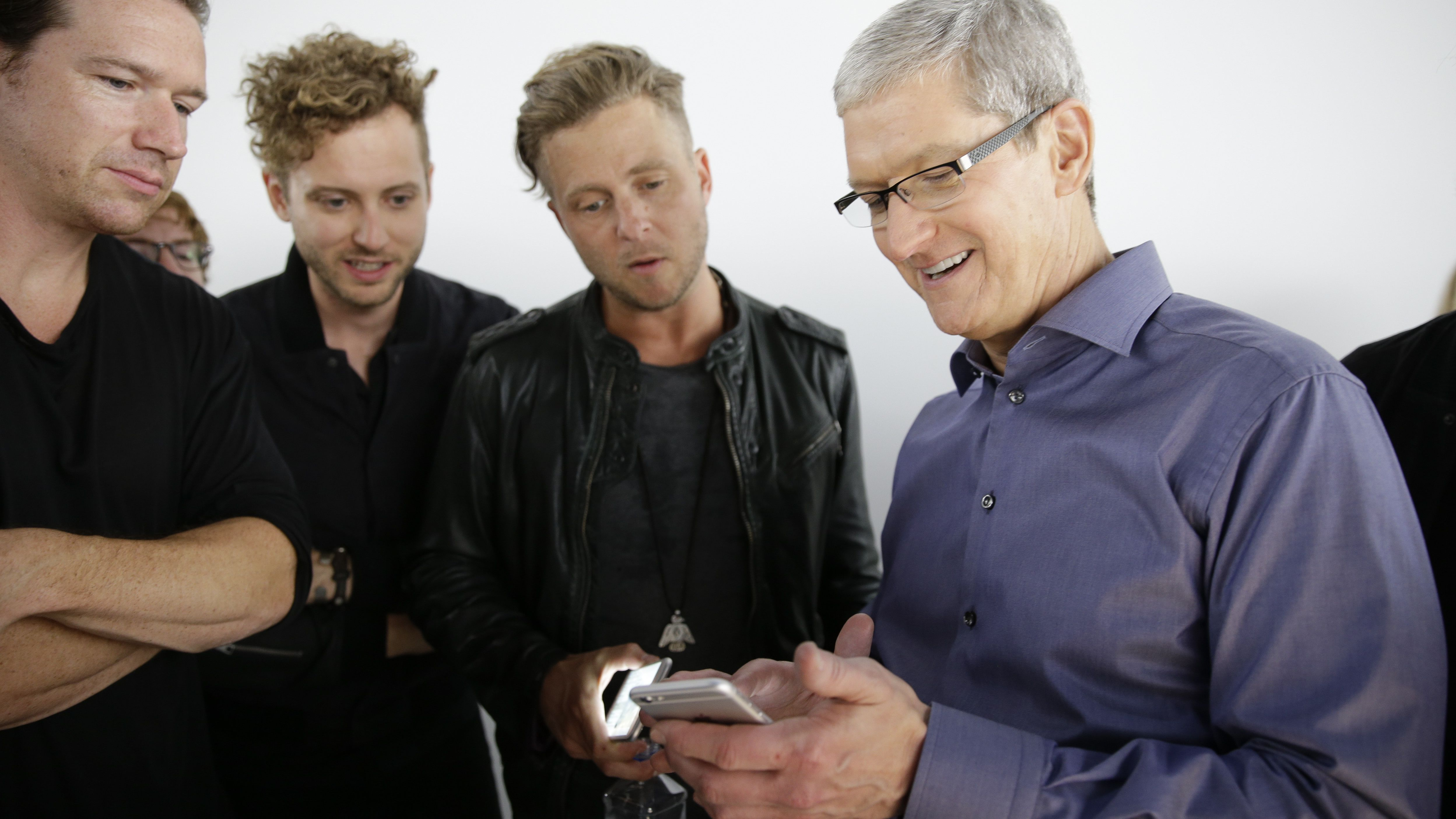 Apple CEO Tim Cook, right, looks at the new iPhone 6s with the members of OneRepublic, in the demo room after Apple event at the Bill Graham Civic Auditorium in San Francisco, Wednesday, Sept. 9, 2015. (AP Photo/Eric Risberg)