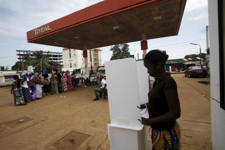 A woman casts her vote at a petrol station in Conakry.
