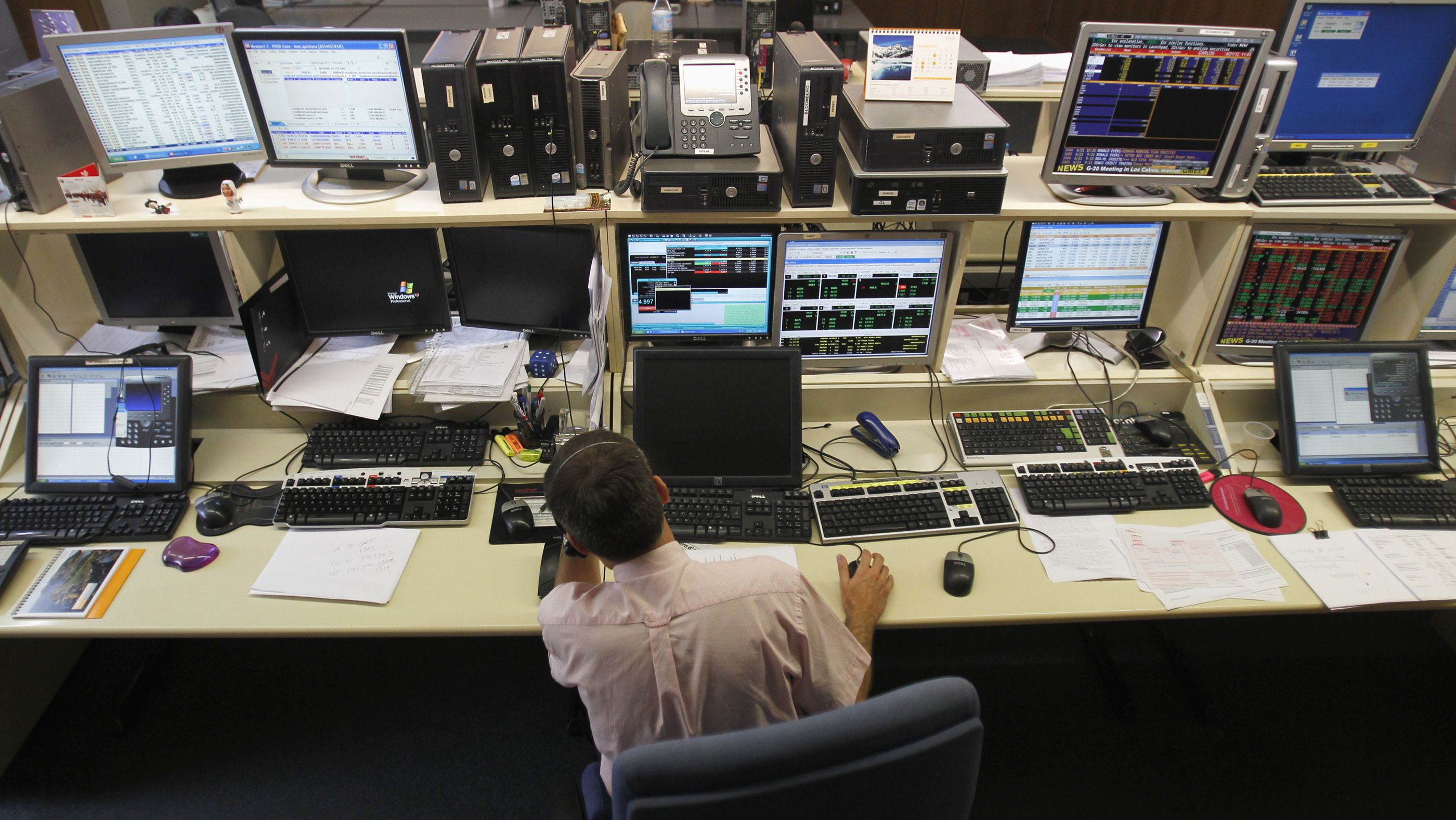 A trader looks at computer screens during Spain's bonds auction in a broker's office in Barcelona June 21, 2012.