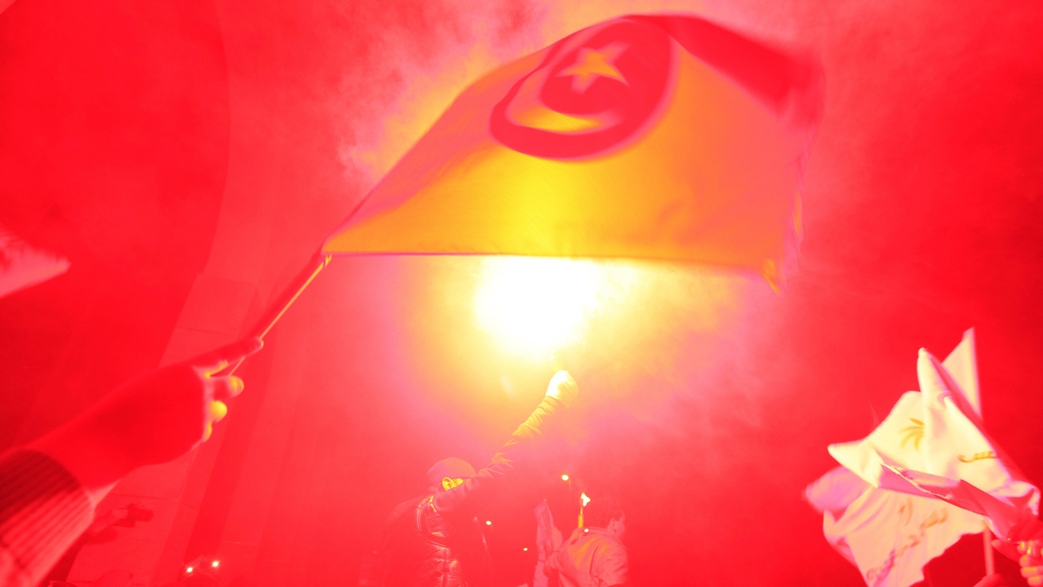 Supporters of the Nidaa Tounes (Call for Tunisia) secular party movement wave the national flag and shout slogans amidst lighted flares outside Nidaa Tounes in Tunis December 21, 2014.