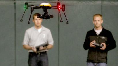 FILE - In this June 24, 2014 file photo, Jake Stoltz, left, and Trevor Woods of the John D. Odegard School of Aerospace Sciences at the University of North Dakota in Grand Forks, remotely pilot a Draganflyer X4ES drone during a demonstration at the Alerus Center in Grand Forks, N.D. Organizers of an annual unmanned aircraft conference are calling North Dakota the Silicon Valley of the drone world. Some of the top aerospace experts in the country are meeting Wednesday, Sept. 23, 2015, in Grand Forks to talk about research and business opportunities in the state. (AP Photo/Bruce Crummy, File)