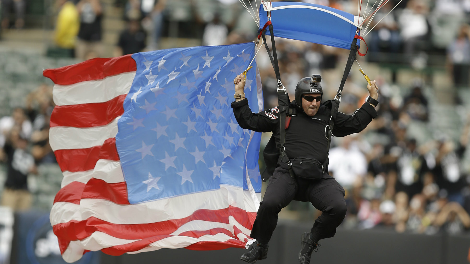 A man parachutes into O.co Coliseum with an American flag before an NFL football game between the Oakland Raiders and the Cincinnati Bengals in Oakland, California.