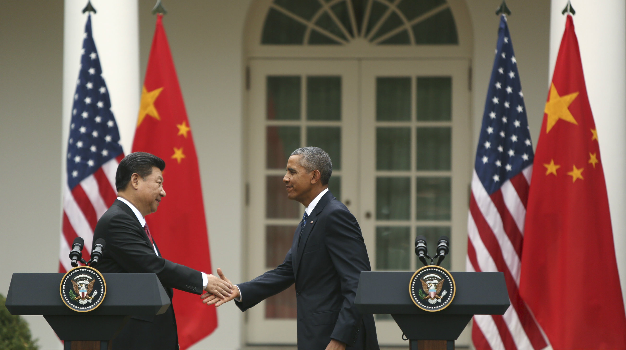 Xi Jinping and Barack Obama shake hands after announcing an agreement not to support cybertheft of each others' corporate trade secrets.