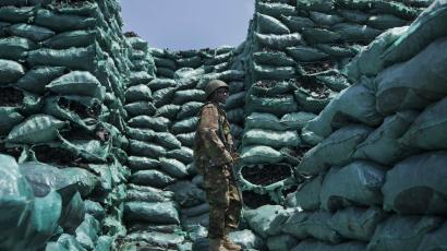A Kenyan soldier stands amongst piles of charcoal in Somalia.
