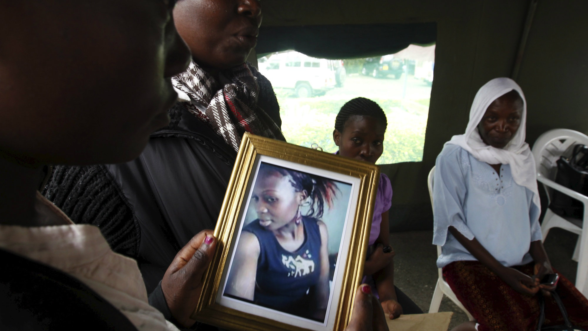 A relative carries a picture of a student killed in an attack on Garissa University in April.