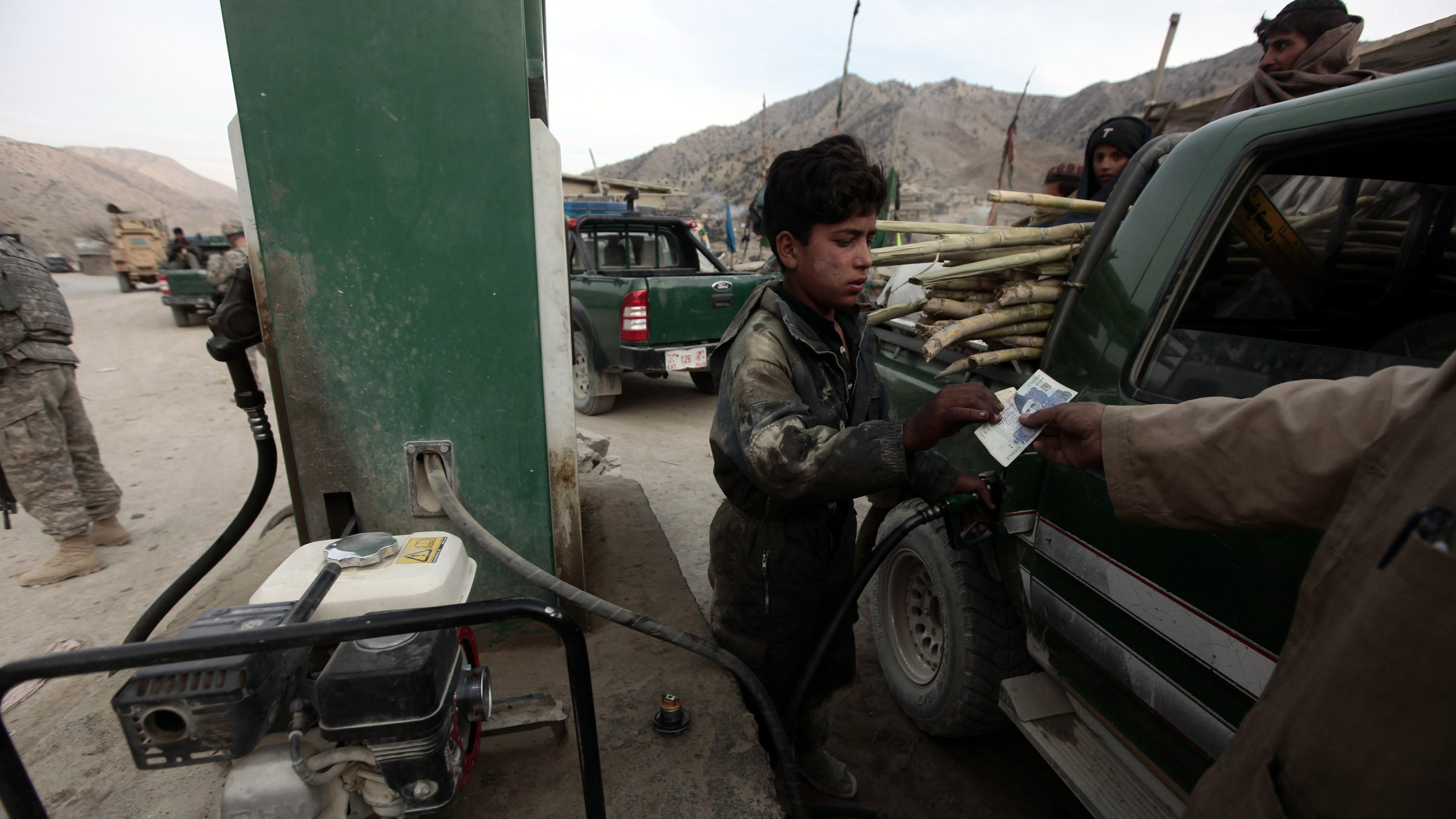 An Afghan employee fills a car with petrol at a gas station in the town of Saway-kowt in Khowst province, Afghanistan, December 26, 2009.