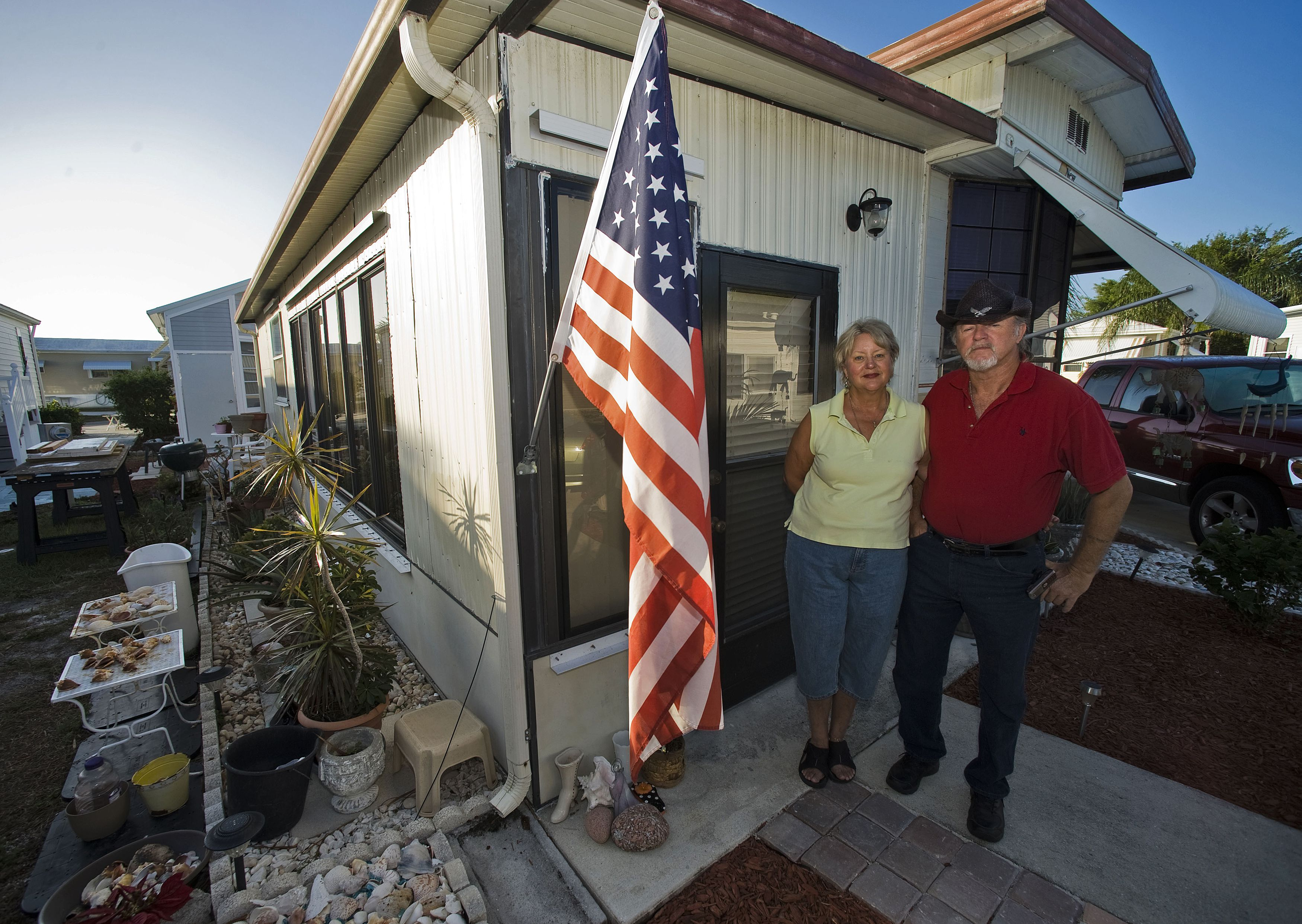 """Andrea Davis and Dewey Schilling stand outside their home at Limetree Park where they live year-round in Bonita Springs, Florida, March 23, 2012. Davis, 63, a former secretary, said she hadn't worked long enough at one place to build up a 401K. """"If it weren't for Social Security, I would probably be on the street,"""" she added."""