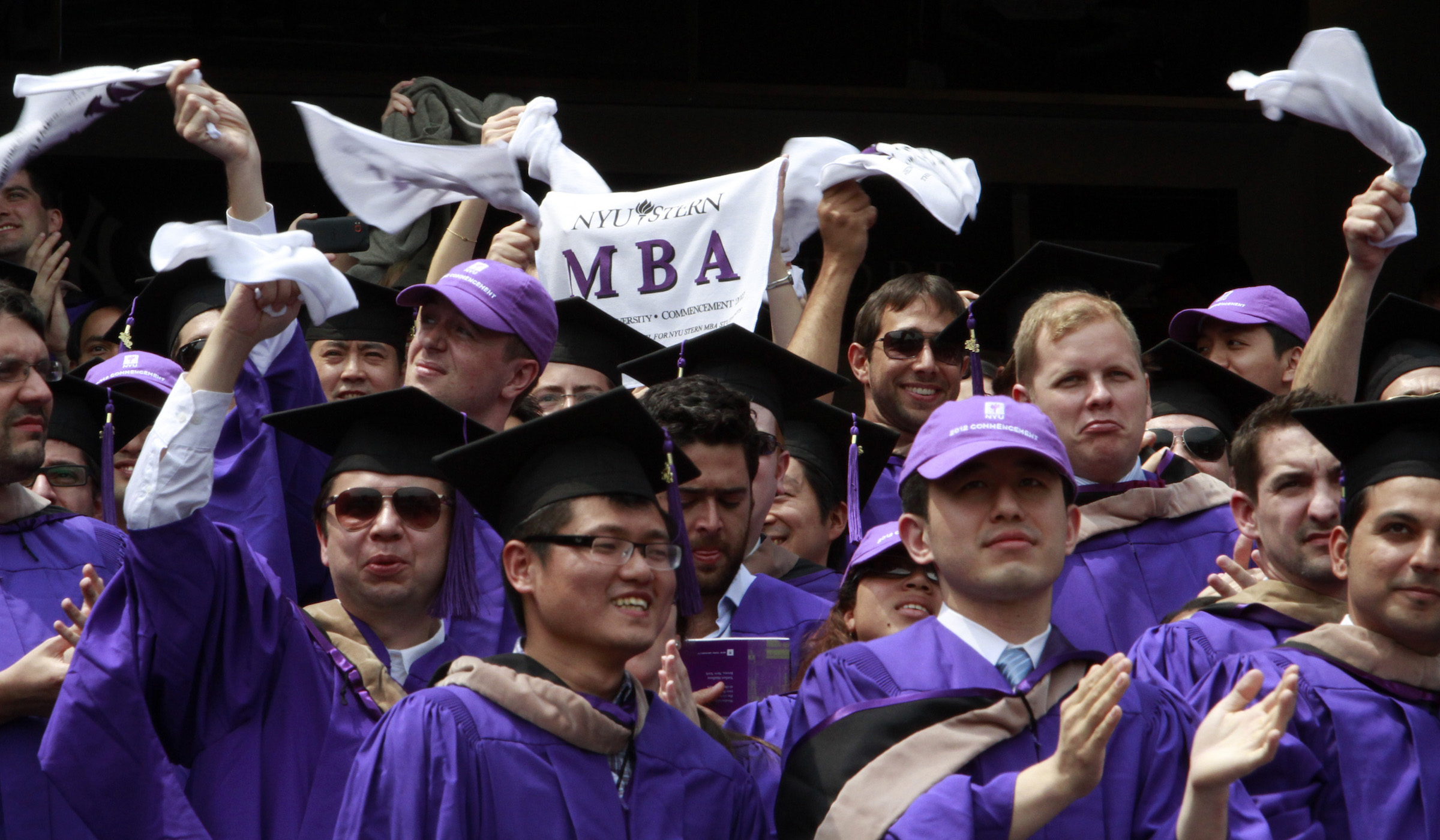 """Graduates from the Leonard N. Stern School of Business cheer and wave """"MBA"""" towels as they are declared degree candidates, during the New York University 180th commencement ceremony at Yankee Stadium on Wednesday, May 16, 2012 in New York."""