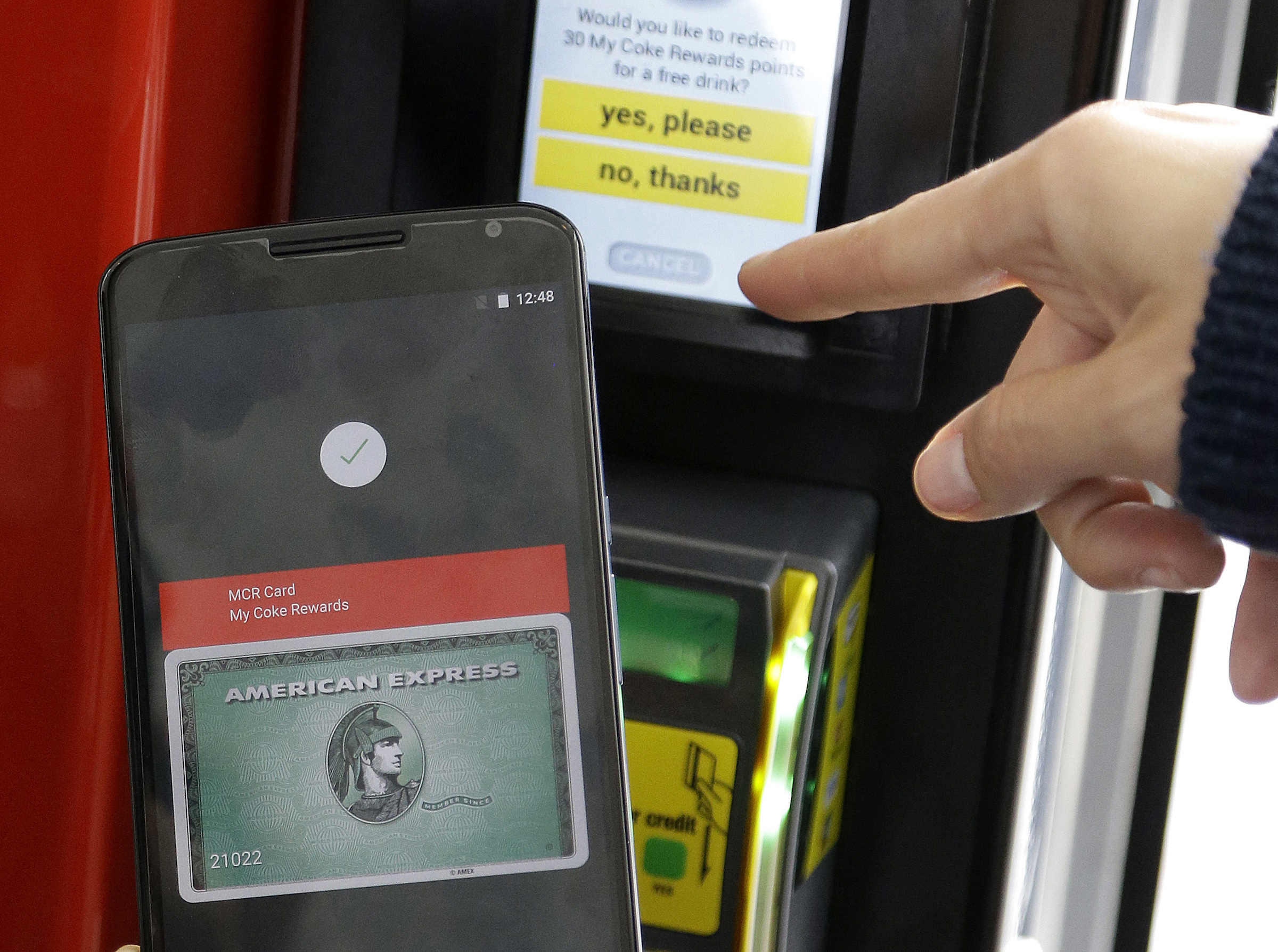 In this May 28, 2015 file photo, a Google employee gives a demonstration of Android Pay on a phone at Google I/O 2015 in San Francisco. Google's next version of its Android operating system will boast new ways to fetch information, pay merchants and protect privacy on mobile devices as the Internet company duels with Apple in the quest to make their technology indispensable.