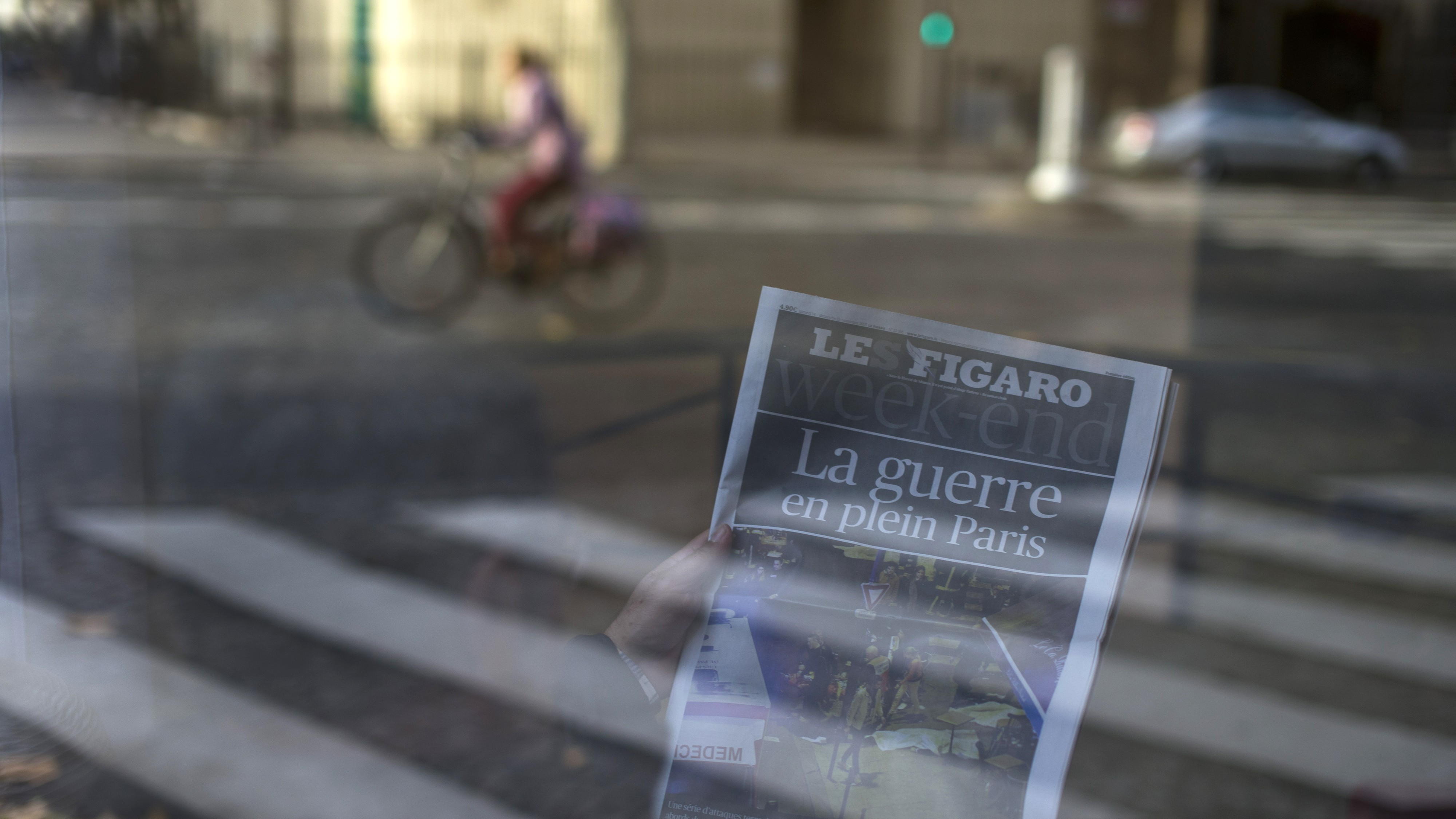 """A man reads a newspaper with a headline reading """"War in the heart of Paris"""" in a hotel lobby in Paris, France, Saturday, Nov. 14, 2015. French police are hunting possible accomplices of eight assailants who terrorized Paris concert-goers, cafe diners and soccer fans in this country's deadliest peacetime attacks, a succession of explosions and shootings that cast a dark shadow over this luminous tourist destination. (AP Photo/Peter Dejong)"""