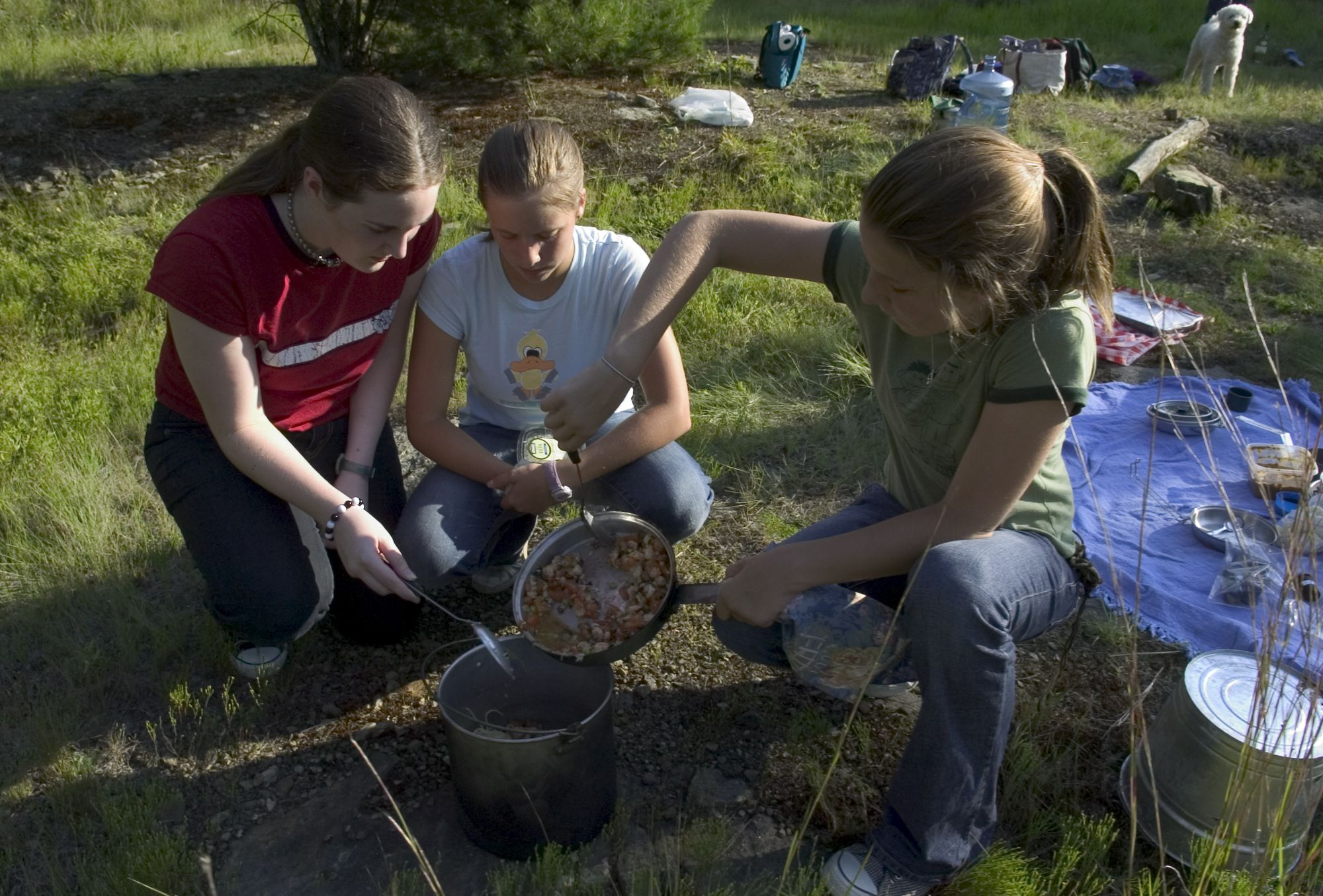 ** FOR USE WITH AP WEEKLY FEATURES **  Girl Scouts Hayden Parker, left, Elle Girard, center, and Samantha Westray mix the final ingredients into a pot of pasta at a cookout Monday, Aug. 9, 2004, in Westport, Conn. The 13-year-olds were trying out their skills at outdoor cooking, using gear portable in backpacks. (AP Photo/Douglas Healey)