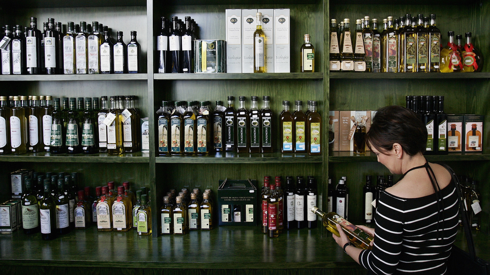 A customer chooses an extra virgin olive oil bottle in a specialized shop in center of Madrid, Friday July 29, 2005. Spain is suffering a drought as a result of the driest winter and spring in the last 60 years raising the olive oil prices.