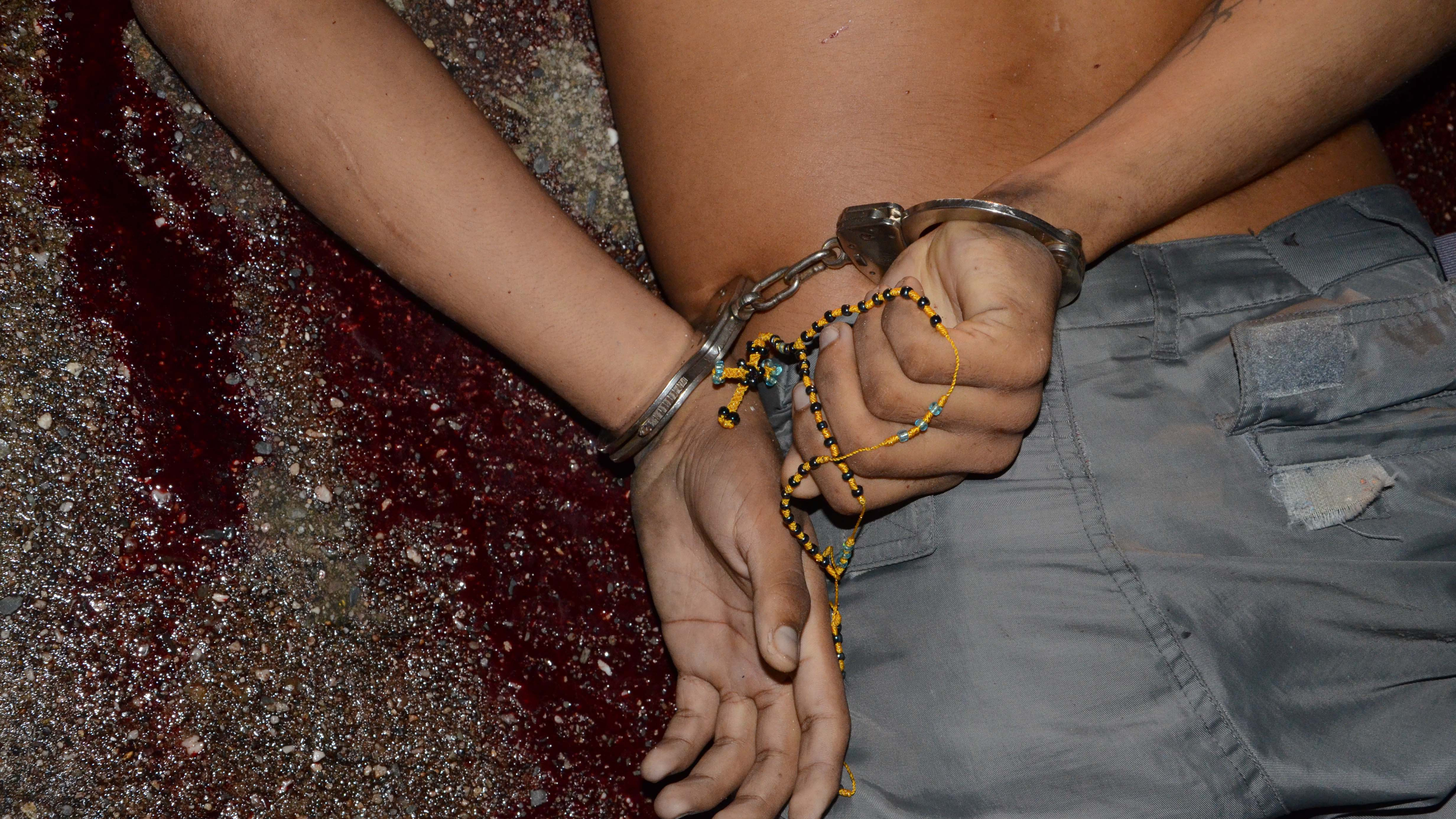 A man lies face down, handcuffed behind his back and holding a rosary after he was shot multiple times in Acapulco, Mexico