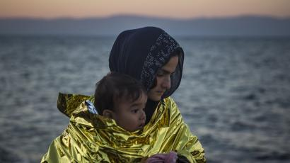 A woman wearing a thermal blanket holds her child on a beach on the Greek island of Lesbos shortly after crossing the Aegean sea on a dinghy