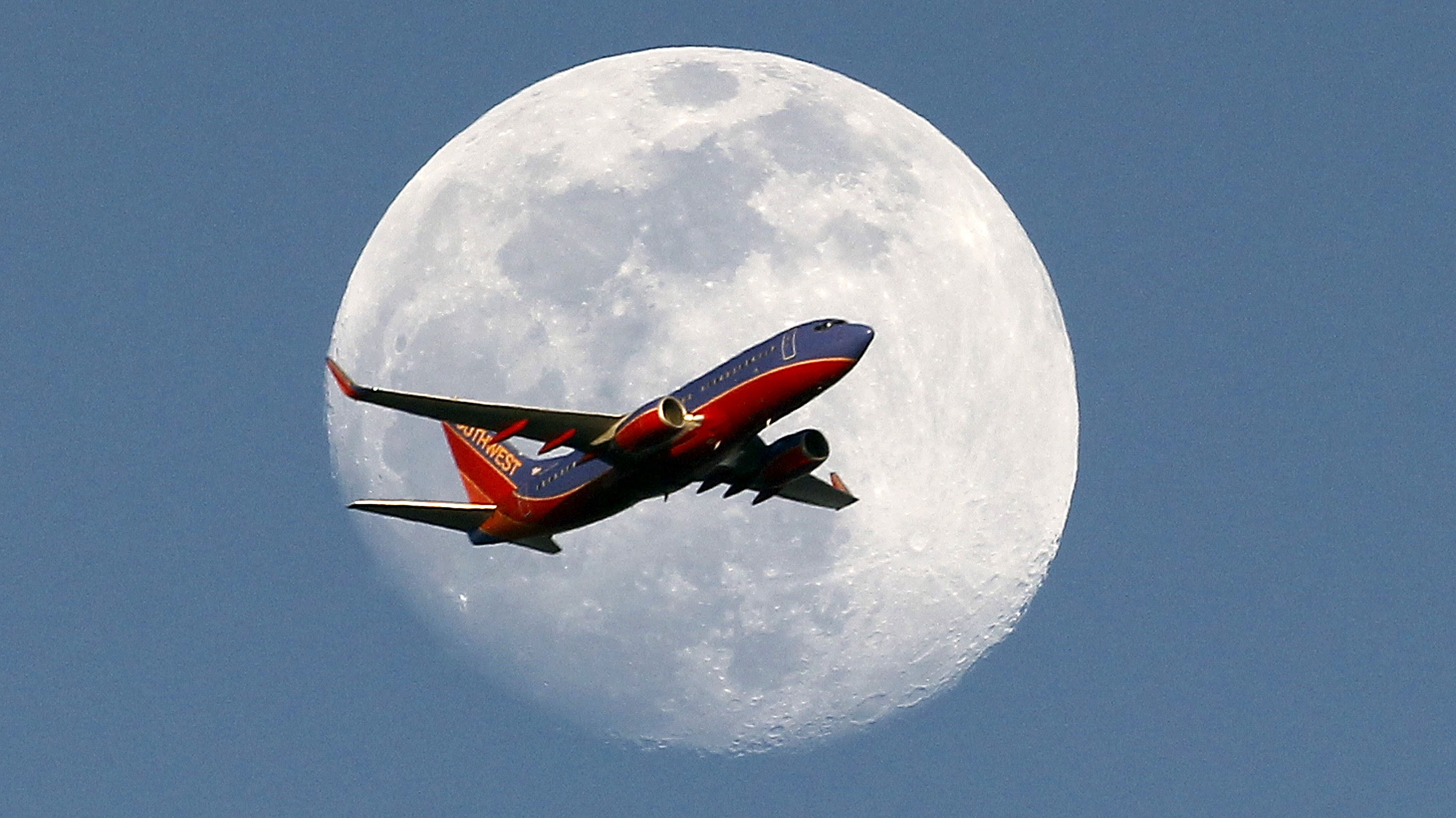 A Southwest Airlines passenger plane crosses the waxing gibbous moon in Whittier, Saturday, May 30, 2015.