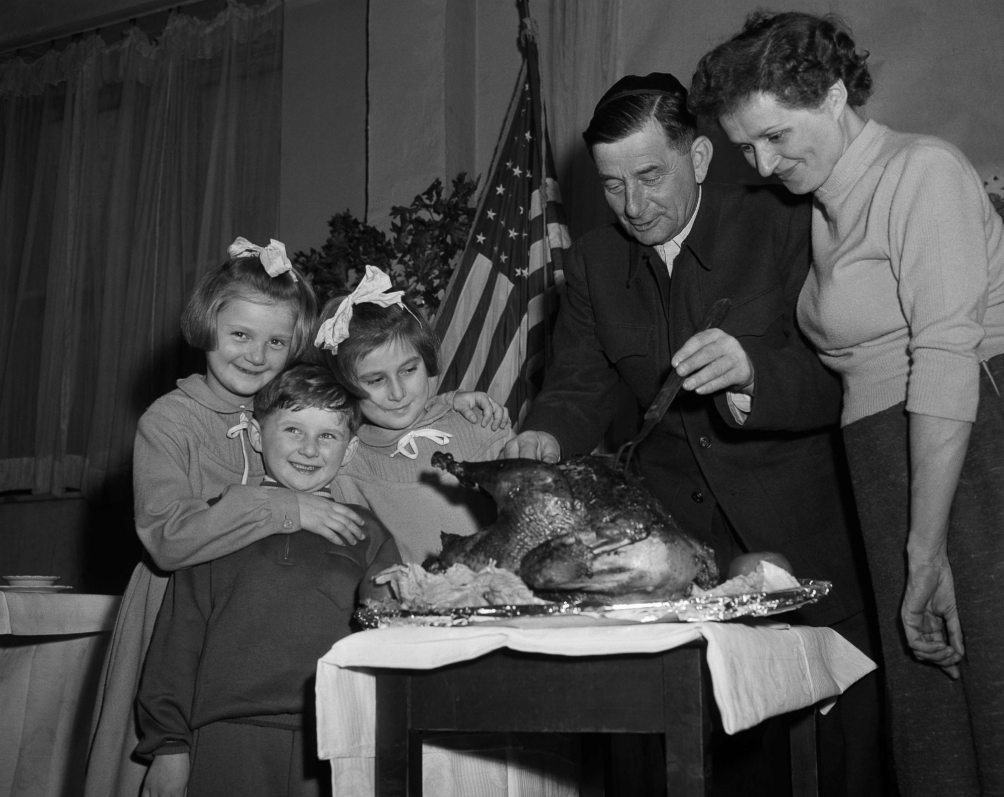 Miksa Frankil, a refugee from Sopron,Hungary, cuts Thanksgiving turkey for his children, from left, Susan, Alex, Edith and his wife Judith on November 22, 1956 in New York. The family arrived with the first group of refugees flown to this country.