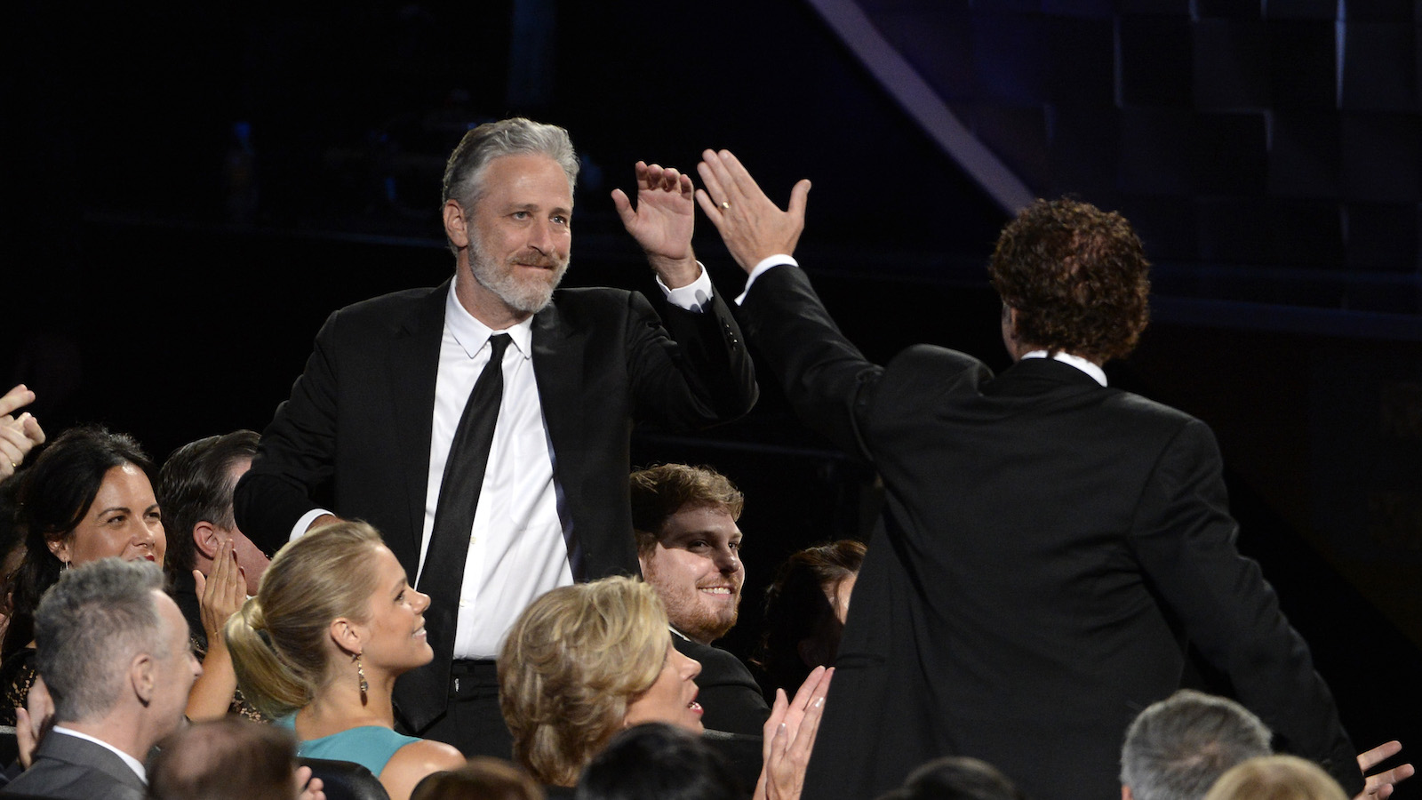 IMAGE DISTRIBUTED FOR THE TELEVISION ACADEMY - Jon Stewart gives Chuck O'Neil a high five at the 67th Primetime Emmy Awards on Sunday, Sept. 20, 2015, at the Microsoft Theater in Los Angeles.