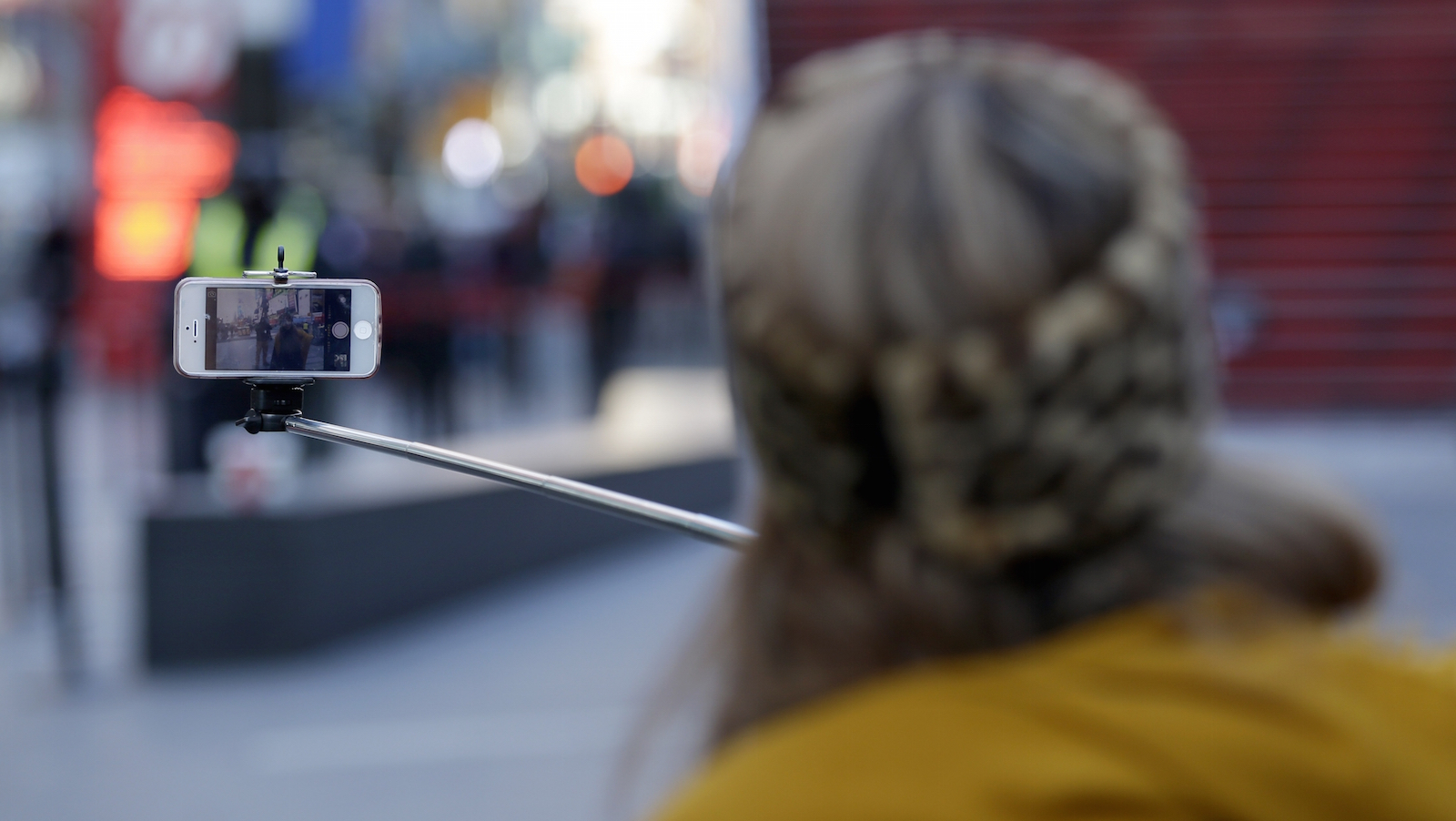 Sandy Johal uses a selfie stick to take a picture of herself in Times Square in New York, Thursday, Jan. 8, 2015. Relatively new gadgets called selfie sticks make it easy to take your own wide-angled self-portraits or group shots. Fans say the expandable rods, which allow users to hold their cellphones a few feet away, are the ultimate convenience: no more bothering passers-by to take pictures, no more fretting about strangers taking lousy shots or running off with a pricey iPhone.