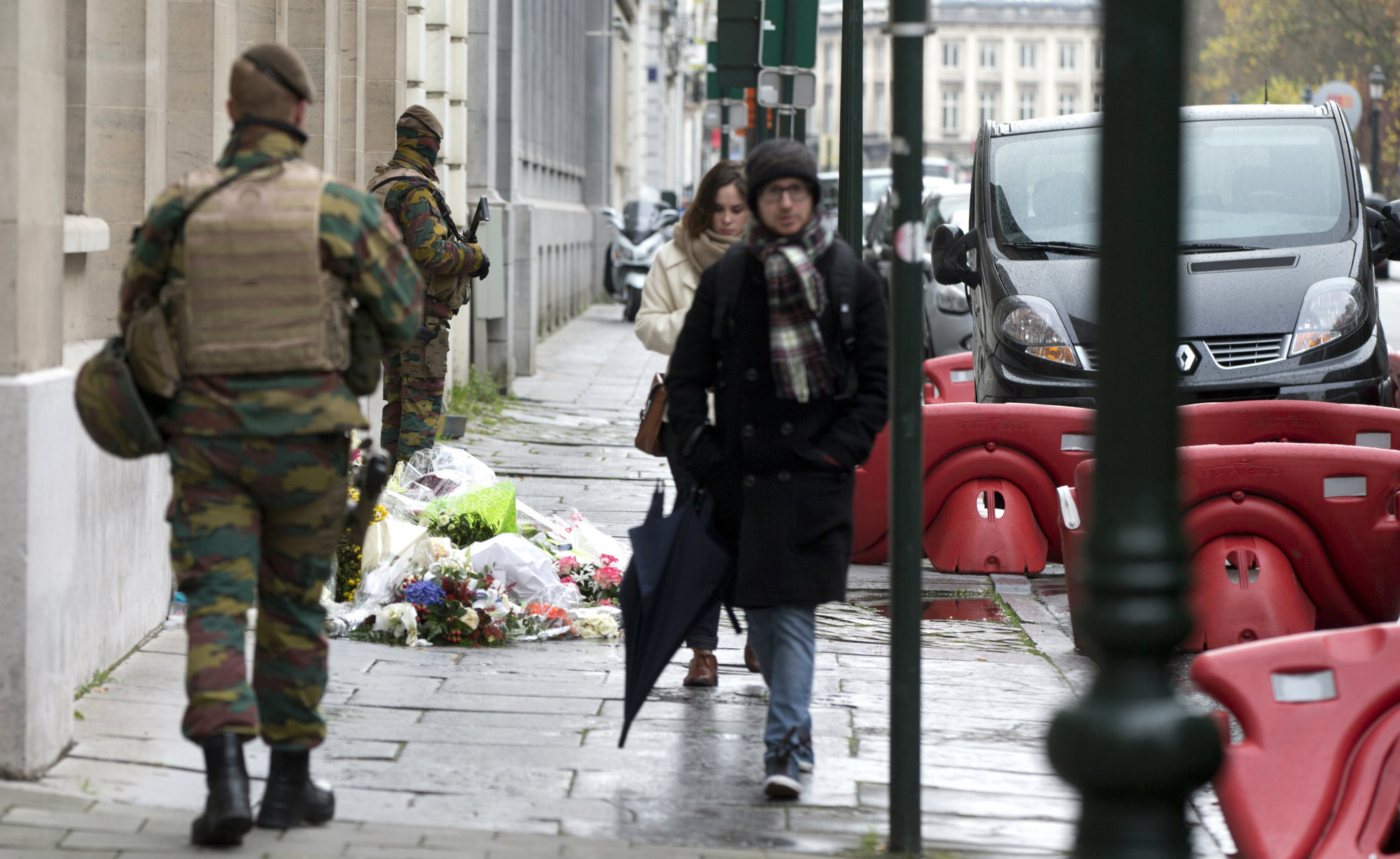 Belgian Army soldiers patrol next to flowers left outside of the French Consulates office in Brussels Saturday, Nov. 21, 2015. Belgium raised it security level to it's highest degree on Saturday as the manhunt continues for extremist Salah Abdeslam who took part in the Paris attacks.