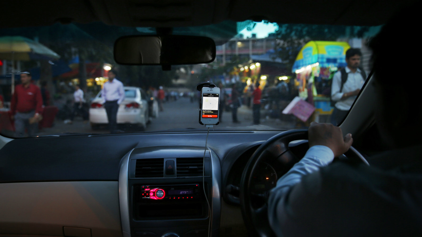 In this Wednesday, March 19, 2014 photo, an Uber taxi driver drives his car through a street in New Delhi, India. Riding on its startup success and flush with fresh capital, taxi-hailing smartphone app Uber is making a big push into Asia. The company has in the last year started operating in 18 cities in Asia and the South Pacific including Seoul, Shanghai, Bangkok, Hong Kong and five Indian cities.