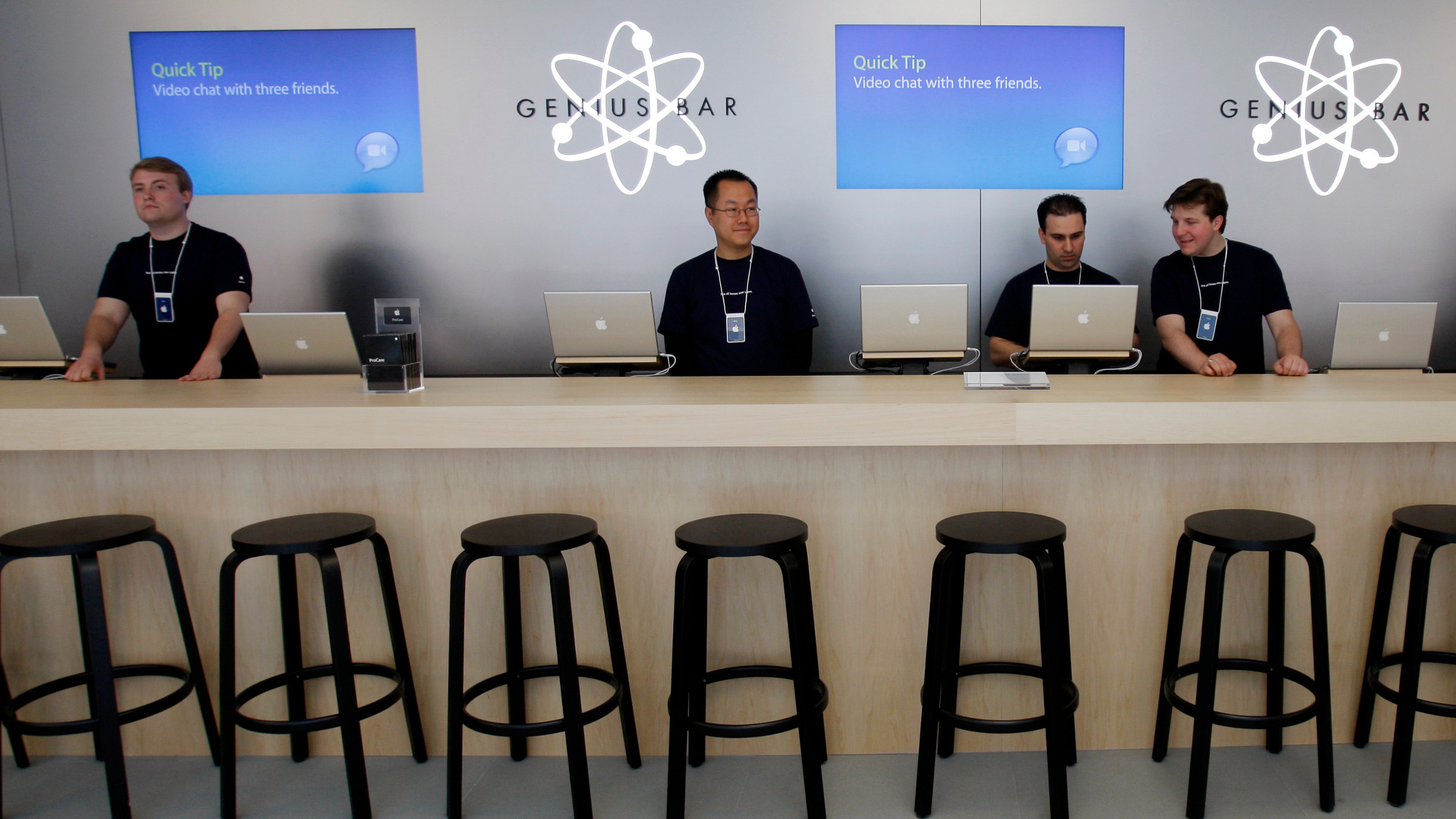 """Apple experts wait at the """"Genius Bar"""" in the new Apple store during the press preview in Boston, Massachusetts May 14, 2008. The store, Apple's largest in the U.S., opens May 15. (UNITED STATES)"""