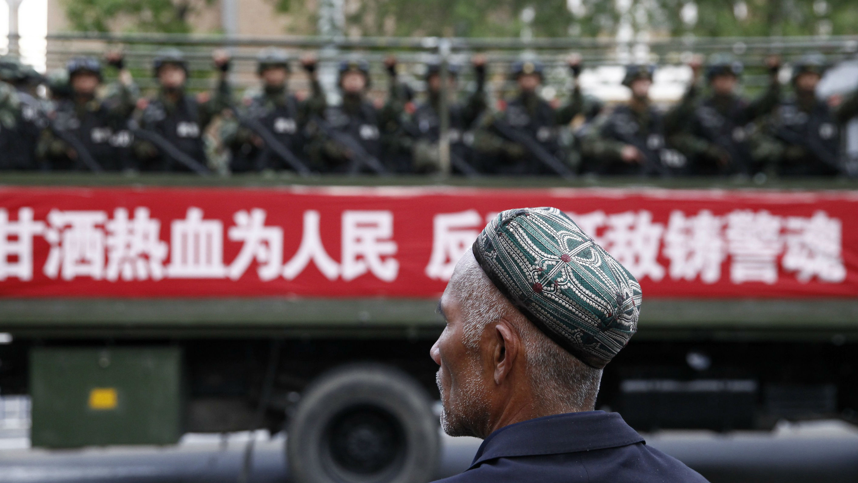 "A Uighur man looks on as a truck carrying paramilitary policemen travel along a street during an anti-terrorism oath-taking rally in Urumqi, Xinjiang Uighur Autonomous Region May 23, 2014. China launched a one-year campaign against terrorist violence in Xinjiang Uighur Autonomous Region on Friday, after 39 people were killed and 94 injured in a terrorist attack on Thursday, Xinhua News Agency reported. The Chinese characters on the banner read, ""Willingness to spill blood for the people. Countering terrorism and fighting the enemies is part of the police spirit."""