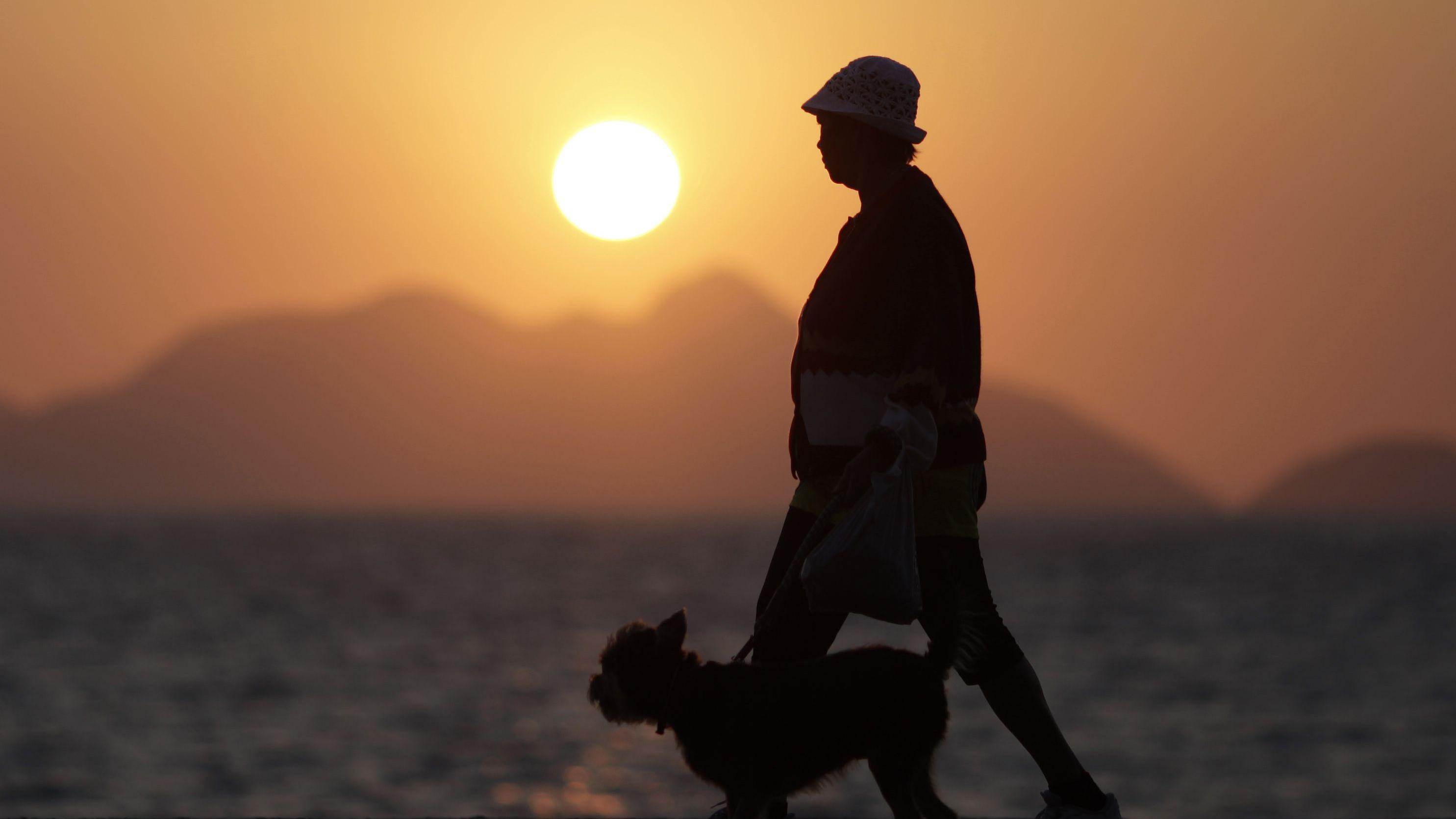 An elderly lady walks with her dog in Copacabana in Rio de Janeiro