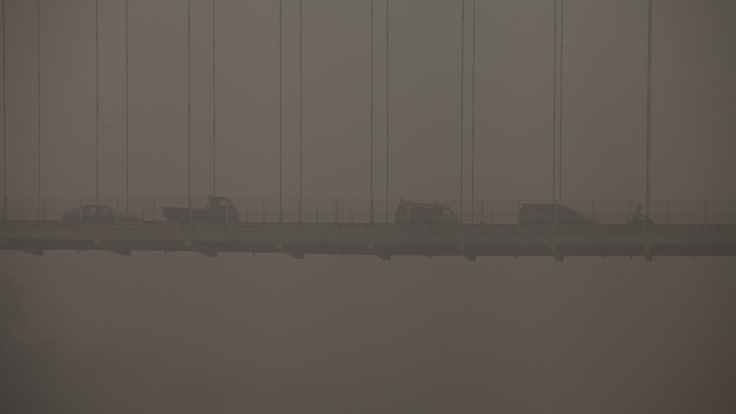 Vehicles drive on a bridge over the Siak river in the haze covered city of Pekanbaru, Riau Province on the Indonesian island of Sumatra