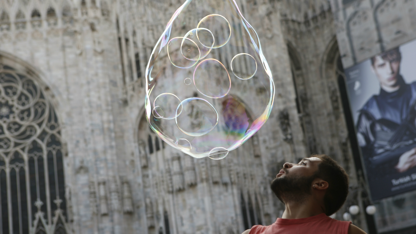 A street artist performs with soap bubbles in front of the Duomo gothic cathedral, in Milan, Italy, Tuesday, Oct. 20, 2015. (AP Photo/Luca Bruno)