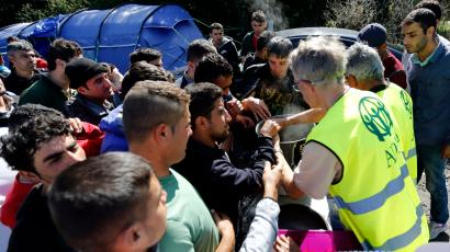 "Migrants receive meals from members of refugee aid organisations during the distribution of food at the makeshift camp called ""The New Jungle"" in Calais, France, September 20, 2015. Around 3,500 migrants and refugees are camped in Calais, fleeing war and poverty in the Middle East, Africa and Asia and now living in the jungle. Most of them are hoping to make the crossing to England. Picture taken September 20, 2015."