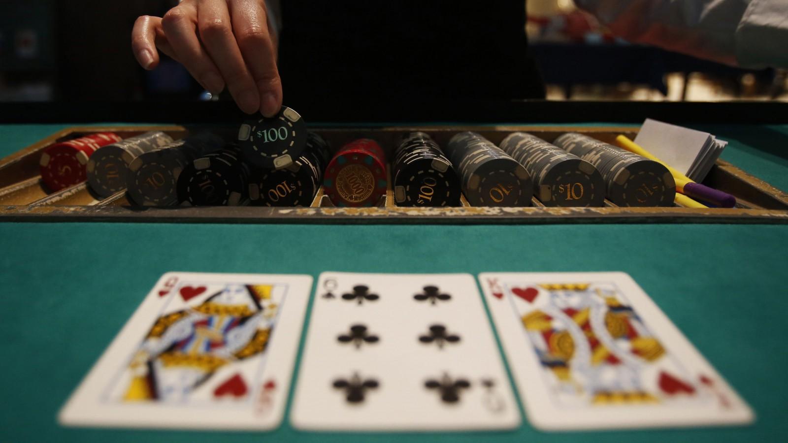 A dealer picks up chips on a mock black jack casino table