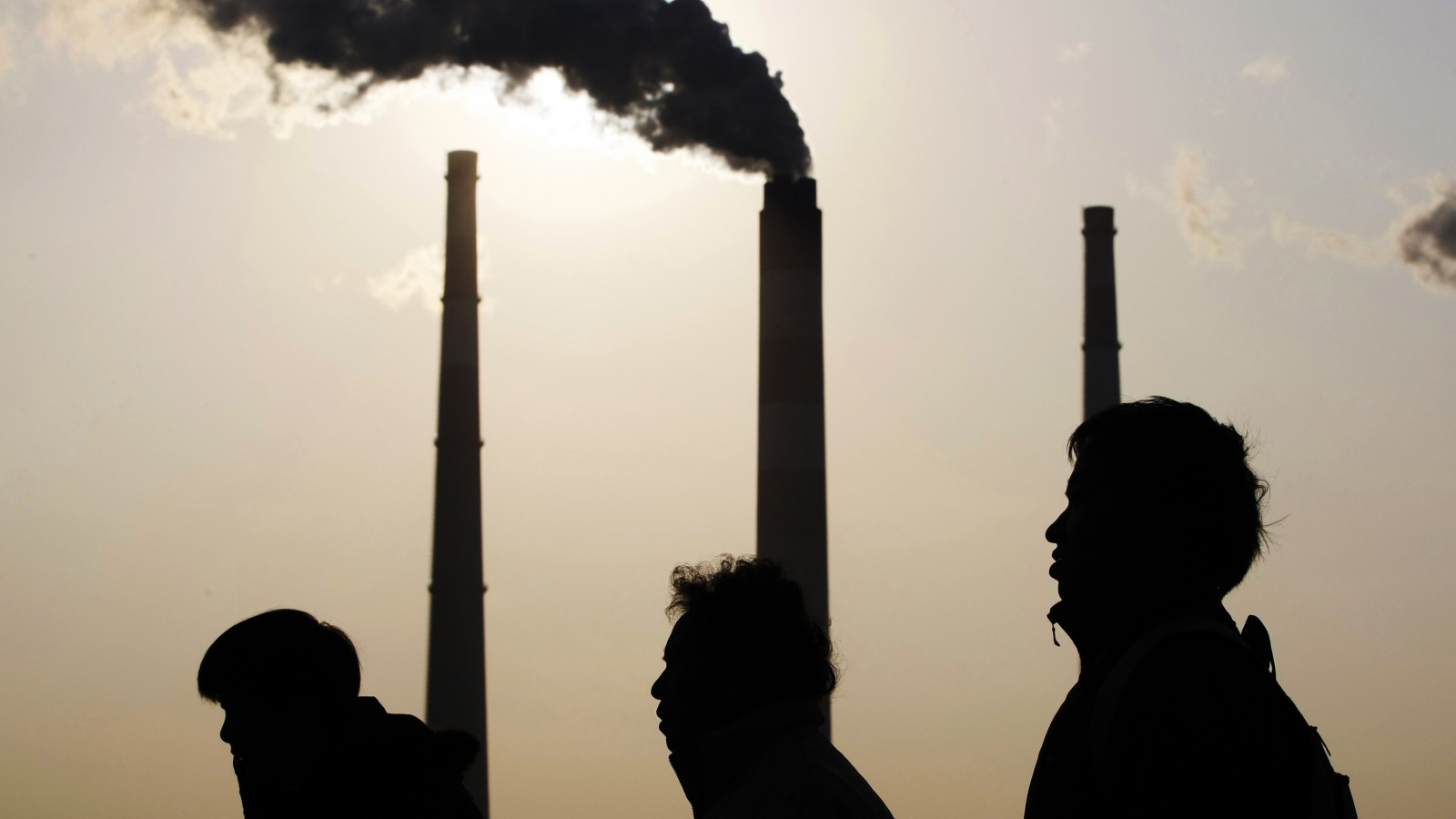 People walk past a power plant in Shanghai December 5, 2009. China's renewable energy strategy through 2050 envisions renewable energy making up one-third of its energy consumption by then, the China Daily said, as the upcoming Copenhagen conference on climate change highlights the world's dependence on fossil fuels. Picture taken December 5, 2009. REUTERS/Aly Song (CHINA BUSINESS ENERGY) - RTXRJ4A