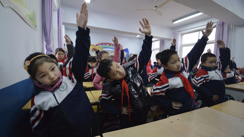 Primary school students practice morning exercises during class break in a classroom in Handan, Hebei province.