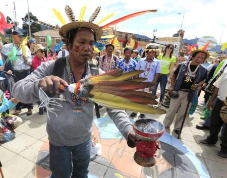 A Colombian Barzano Indian performs a rite ahead of a climate march in Bogota, Colombia.