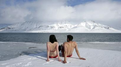 "Climate activists Lesley Butler and Rob Bell (R) ""sunbathe"" on the edge of a frozen fjord in the Norwegian Arctic"