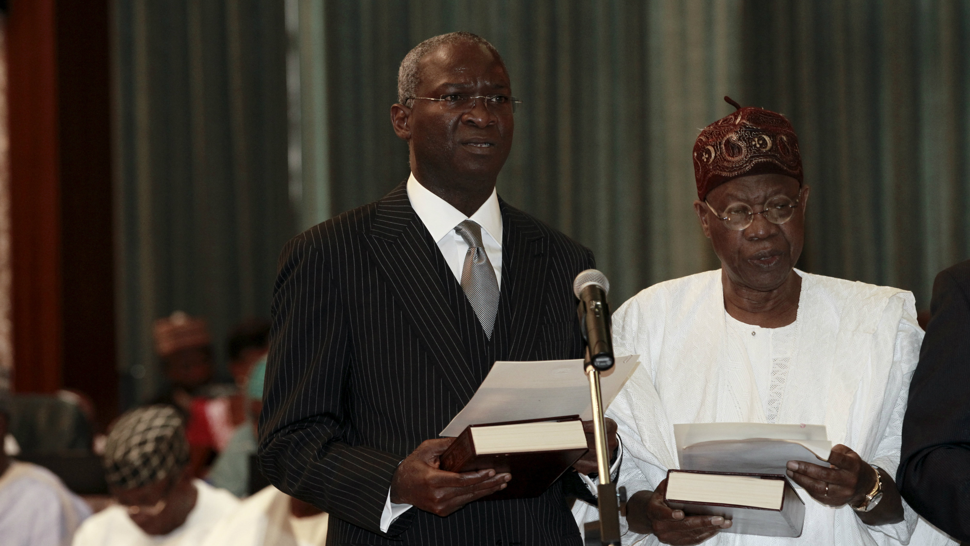 Nigeria's new Power, Works and Housing Minister Babatunde Fashola (front L) and new Information Minister Lai Mohammed take their oath of office during the swearing-in ceremony in Abuja, Nigeria November 11, 2015. Nigeria's President Muhammadu Buhari swore 36 ministers into his cabinet on Wednesday, five months after his inauguration. Buhari won March elections after vowing to crack down on corruption in Africa's biggest economy and top oil producer. He has been criticised for waiting until September to name his ministers at a time when the economy has been hammered by the fall in oil prices. REUTERS/Afolabi Sotunde