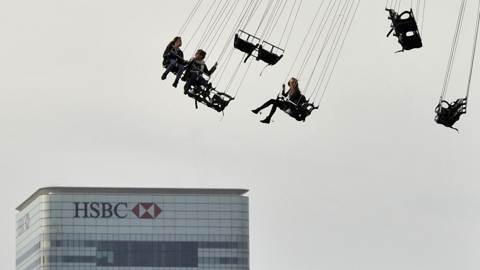 Financial offices of Canary Wharf are seen behind visitors to the O2 arena enjoying a fairground ride in east London November 23, 2011.   REUTERS/Toby Melville (BRITAIN - Tags: BUSINESS SOCIETY) - RTR2UDIM