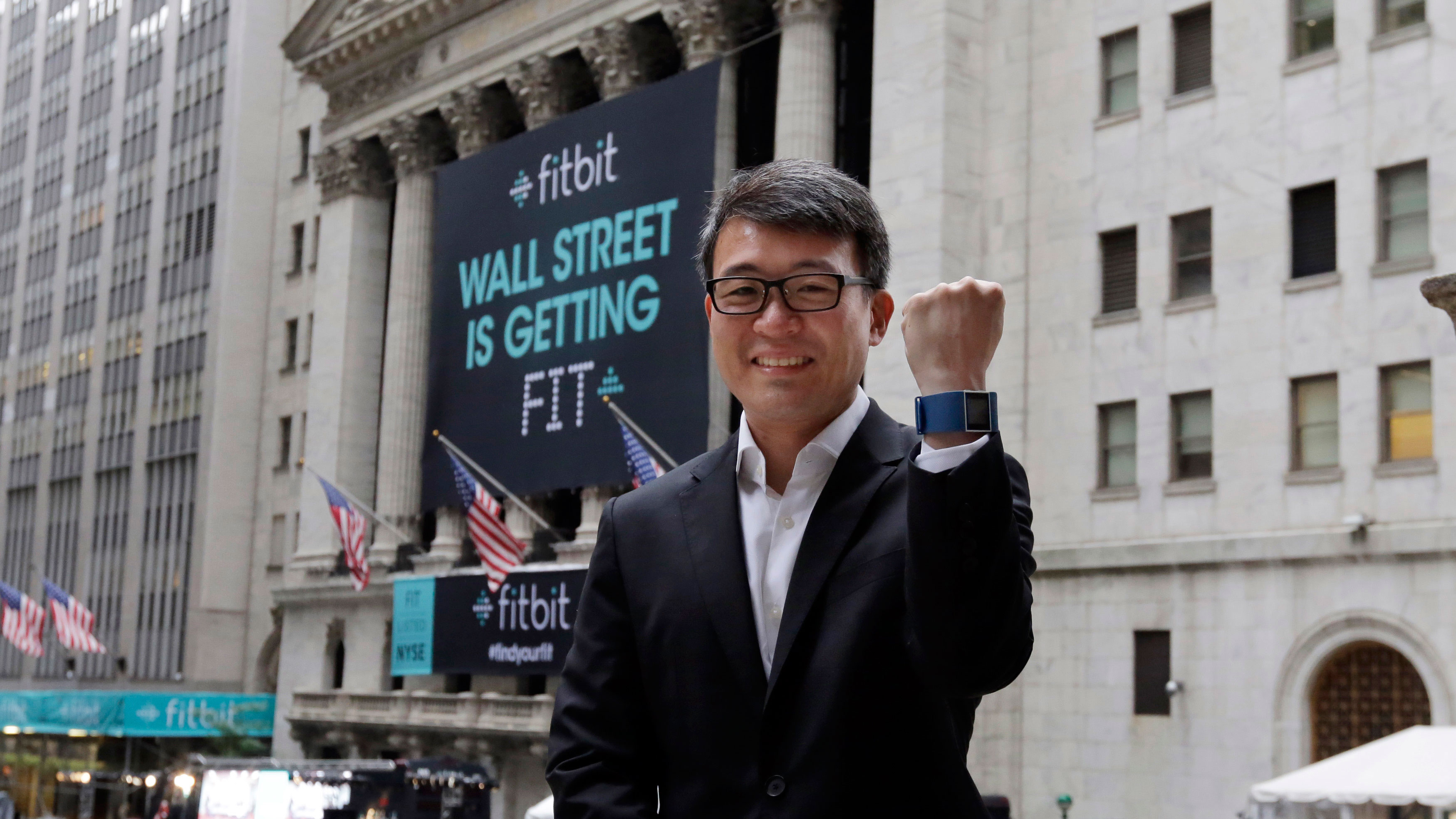 Fitbit CEO James Park shows off one of his devices as he poses for photos outside the New York Stock Exchange, before his company's IPO, Thursday, June 18, 2015. Fitbit makes devices that can be worn on the wrist or clipped to clothing to monitor daily steps, calories burned and grab other data. (AP Photo/Richard Drew)