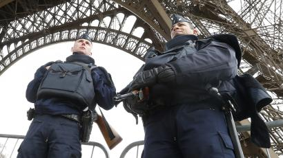 Police take up position under the Eiffel Tower the morning after a series of deadly attacks in Paris