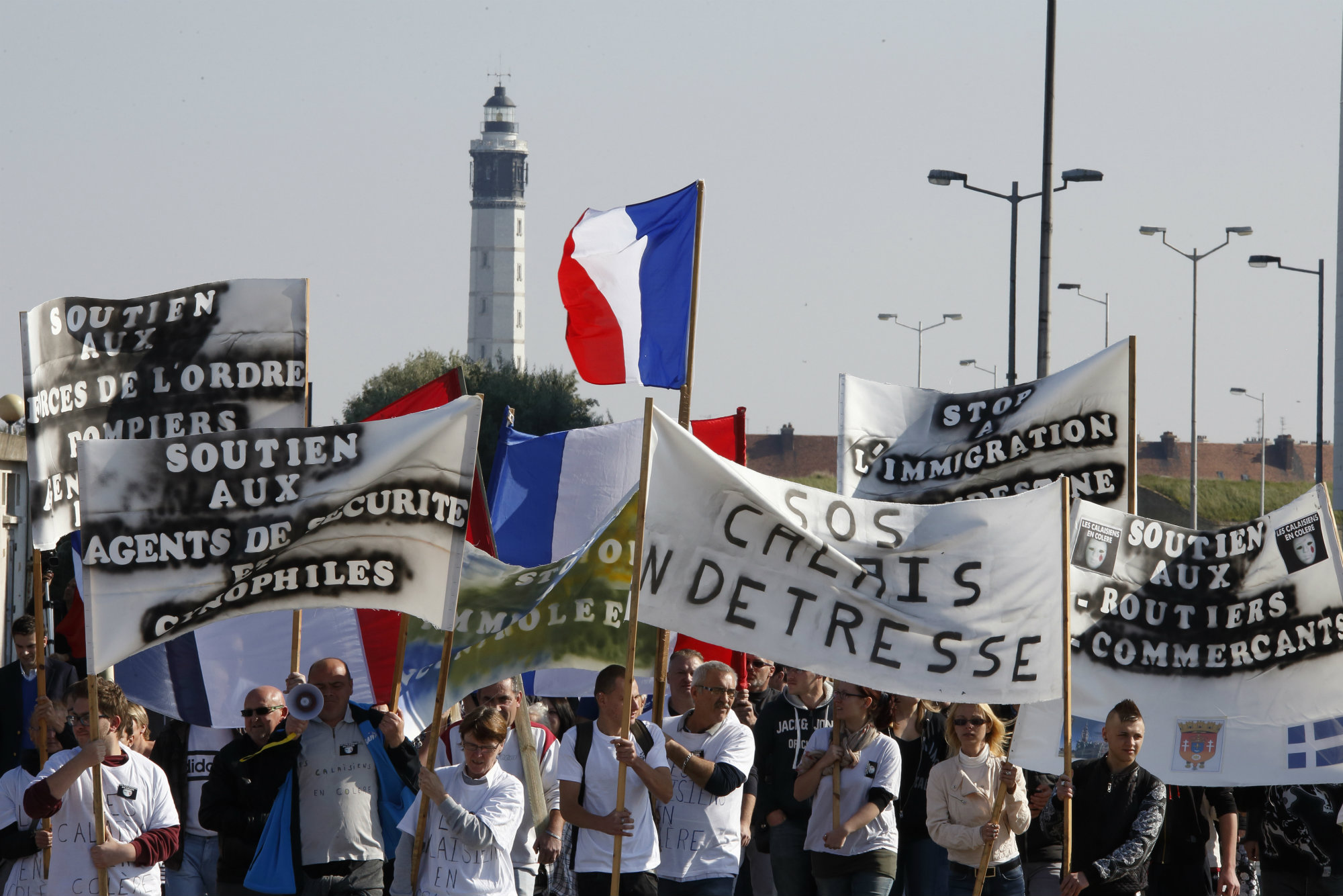 everal hundred people hold banners and wave French flags as they demonstrate against illegal immigration in Calais, France, October 4, 2015. More than 3,000 migrants and refugees fleeing war and poverty in Africa and the Middle East are camped on the French side of the tunnel in Calais, trying to board vehicles heading for Britain via the tunnel and on ferries or by walking through the tunnel, even though security measures aimed at keeping them out have been stepped up. REUTERS/Pascal Rossignol