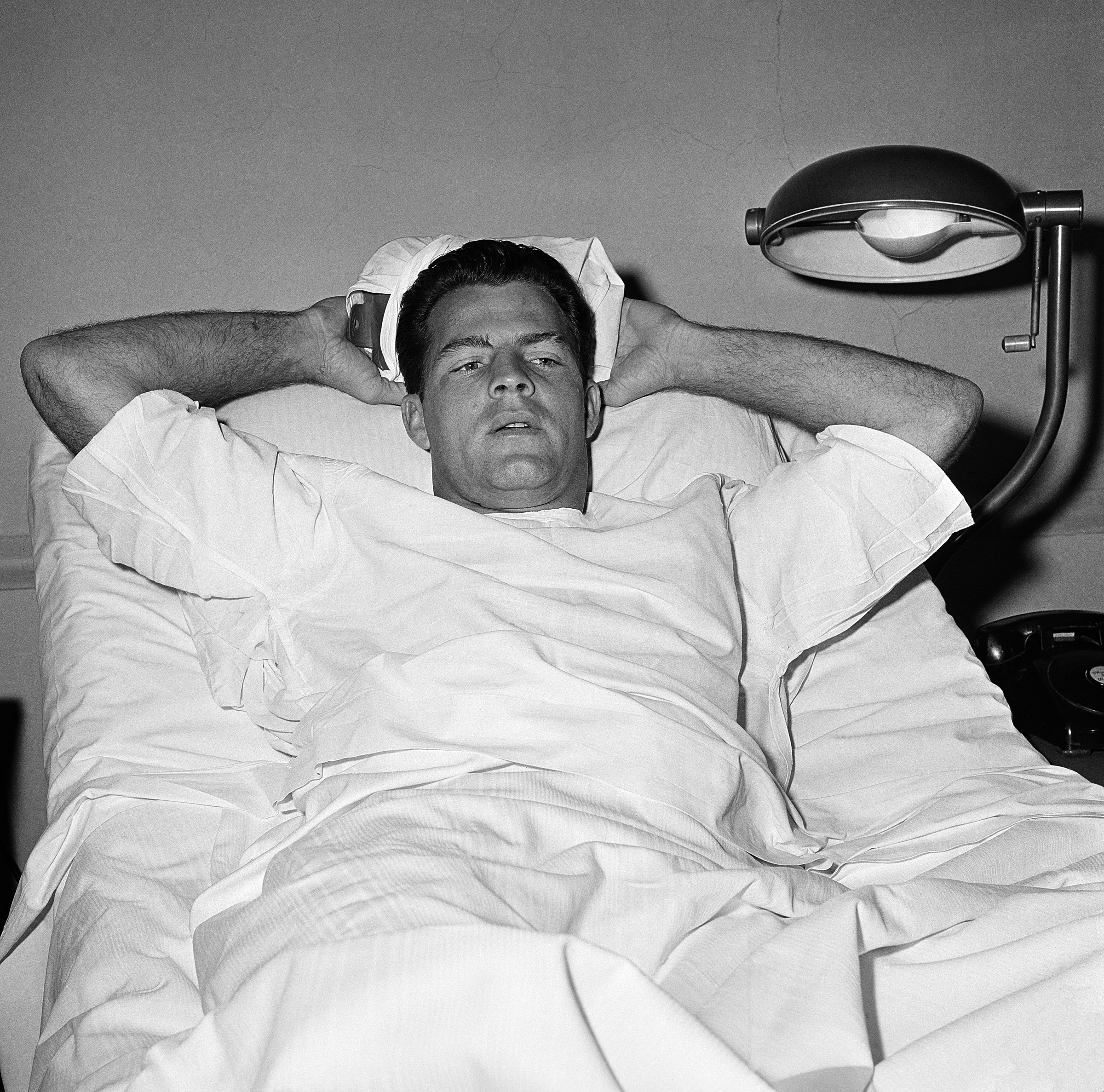 """In this Nov. 22, 1960, file photo, New York Giants football player Frank Gifford lies in a bed holding an ice pack on his head at St. Elizabeth's Hospital in New York. Gifford sustained a consussion in a game on Nov. 20, 1960. The family of Pro Football Hall of Famer Frank Gifford says signs of the degenerative disease chronic traumatic encephalopathy were found in his brain after his death. In a statement released through NBC News on Wednesday, Nov. 25, 2015, the family says Gifford suffered from unspecified """"cognitive and behavioral symptoms"""" in his later years. He died suddenly of natural causes at his Connecticut home in August at age 84. (AP Photo/File)"""