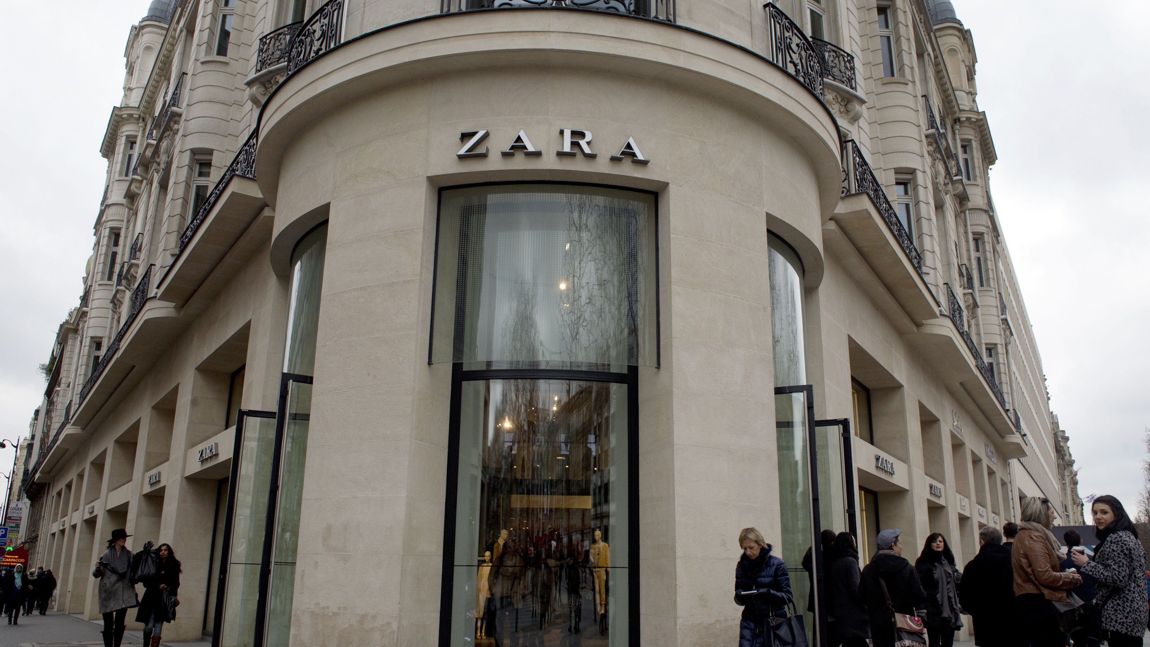People go shopping at a Zara store on the Champs-Elysees avenue in Paris, on February 15, 2015.