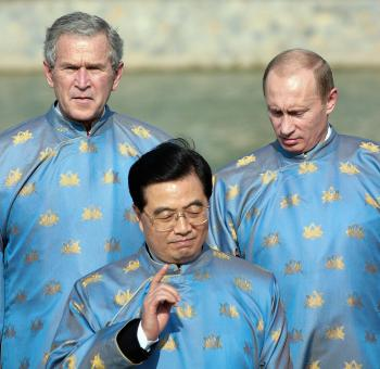Hanoi, VIET NAM: US President George W. Bush (L), Russian President Vladimir Putin (R) and Chinese President Hu Jintao (C), all wearing a Vietnamese 'ao dai' silk tunic, speak as they take part in the official photograph for the Asian Pacific Economic Cooperation (APEC) summit in Hanoi, Vietnam 19 November 2006.
