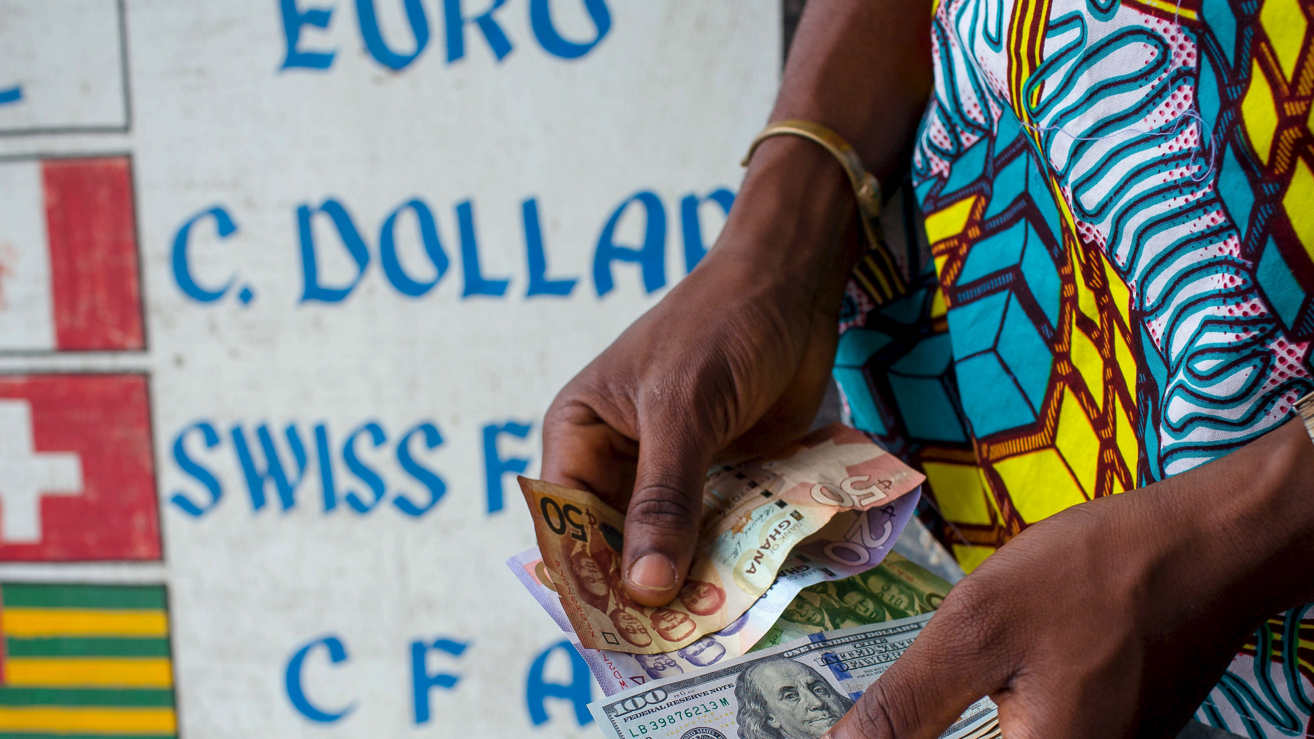 A man trades U.S. dollars for Ghanaian cedis at a currency exchange office in Accra, Ghana