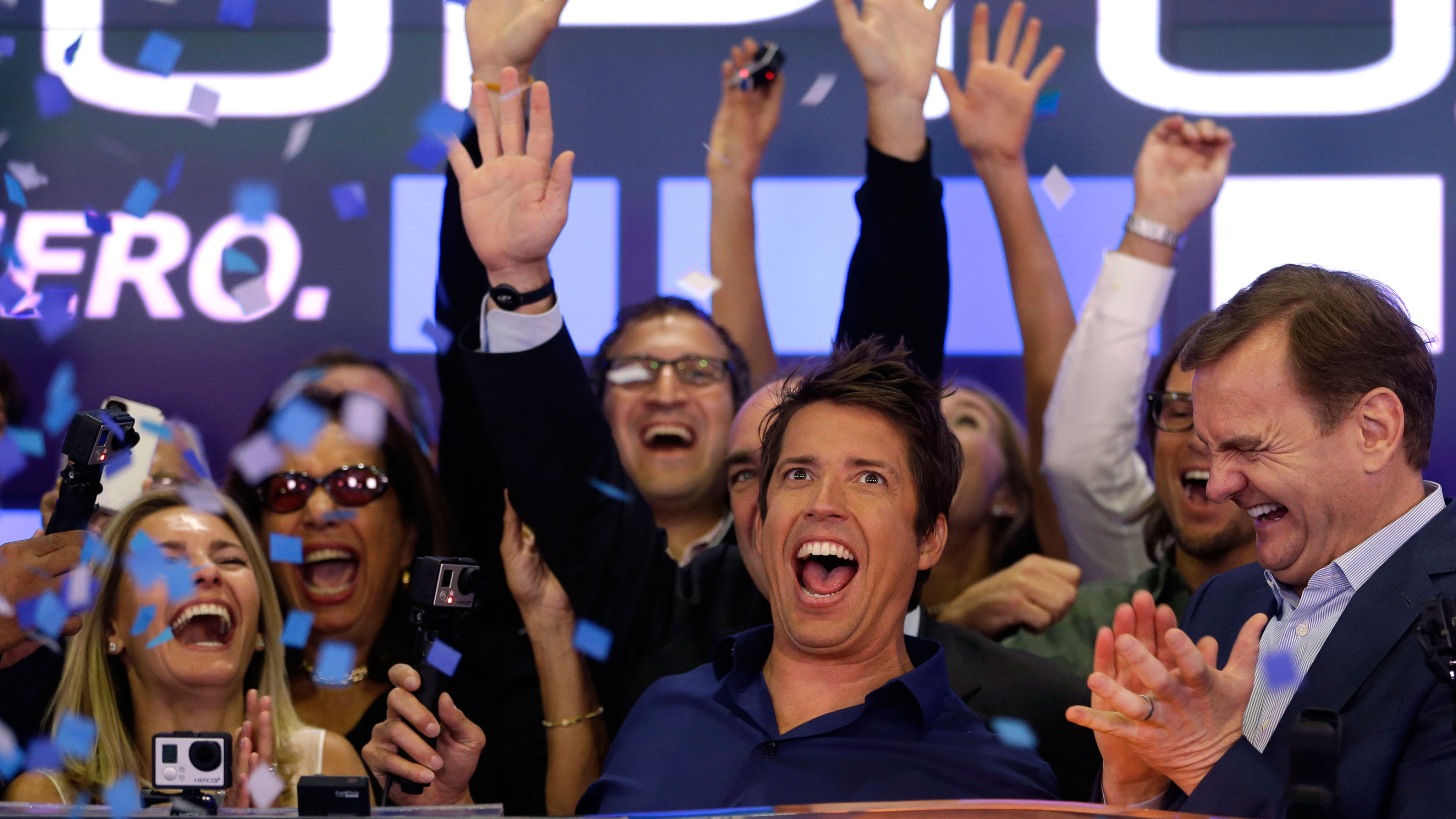 GoPro's CEO Nick Woodman, center, celebrates his company's IPO with family, employees and others at the Nasdaq MarketSite in New York, Thursday, June 26, 2014. GoPro, the maker of wearable sports cameras, loved by mountain climbers, divers, surfers and other extreme sports fans, said late Wednesday it sold 17.8 million shares at $24 each in its initial public offering of stock. (AP Photo/Seth Wenig)