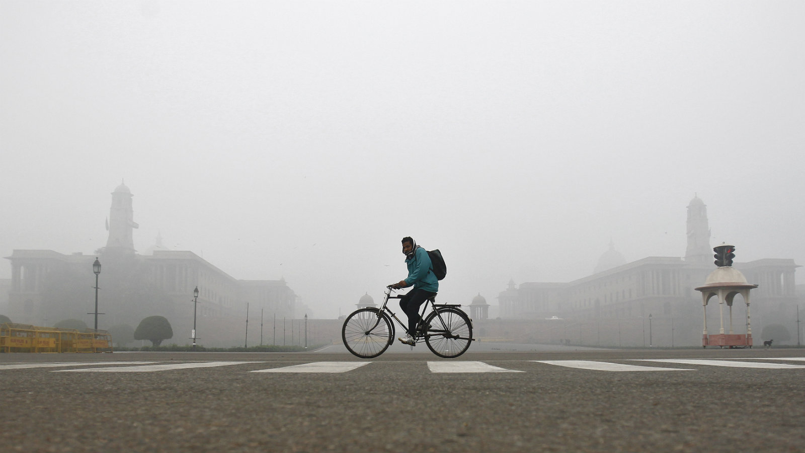 A man rides his bicycle past the Indian Defence (L) and Home Ministries on a cold winter morning in New Delhi December 19, 2013.
