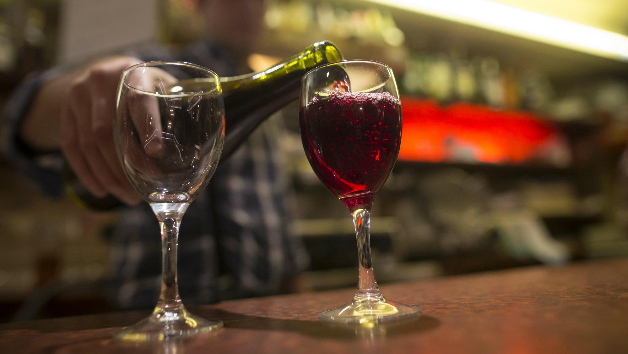 A barman pours a glass of Beaujolais Nouveau wine in a bistrot in Paris, France.