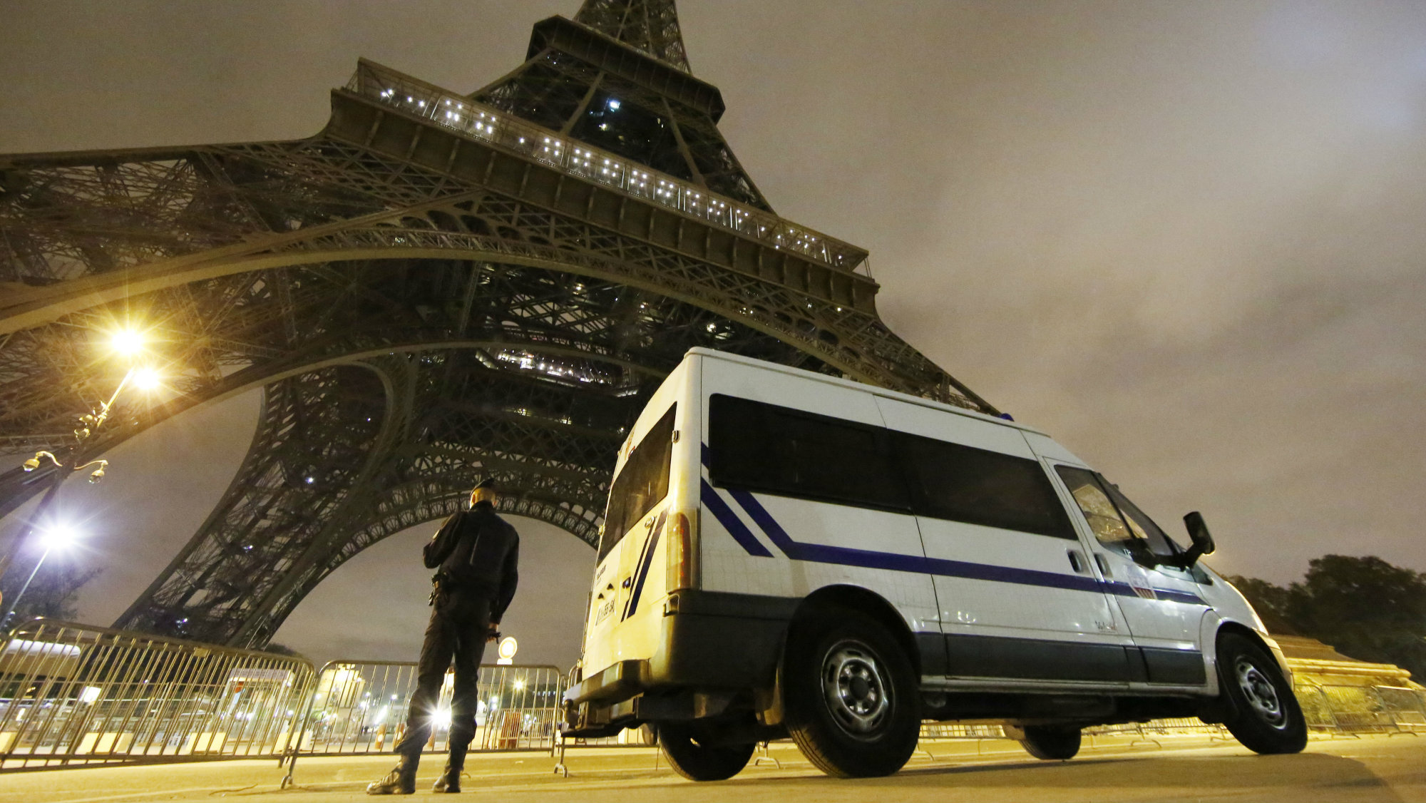 A police officer stands guard at the foot of the Eiffel Tower in Paris.